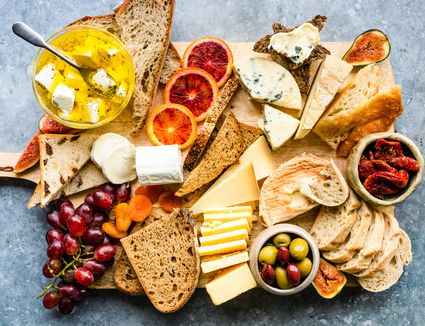 a wooden board with various breads and cheeses