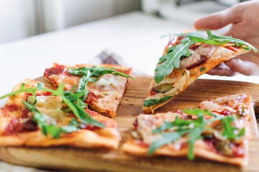 Pizza with mozzarella, chorizo and arugula on wooden cutting board.