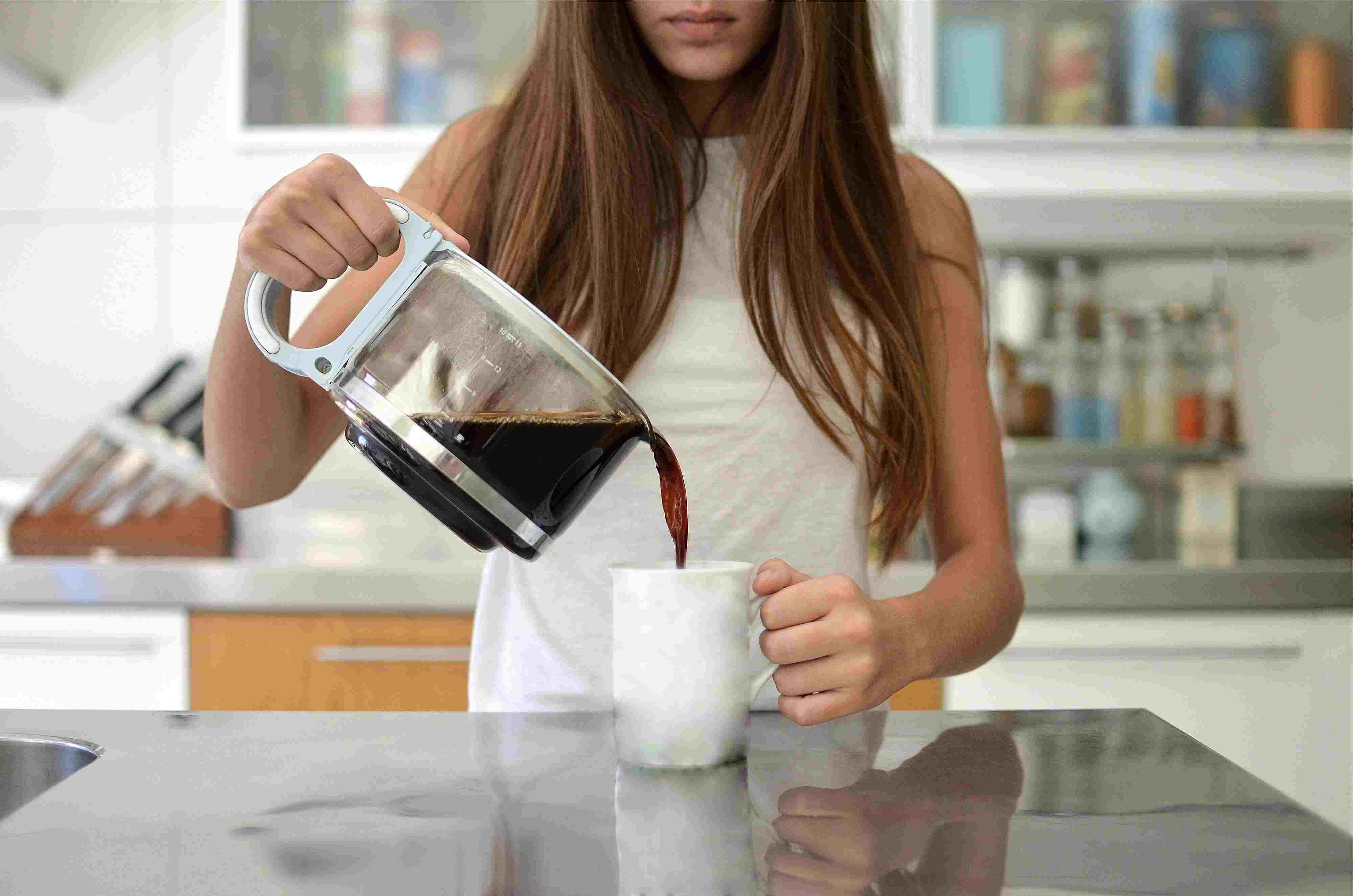 Girl pouring a cup of coffee in the kitchen
