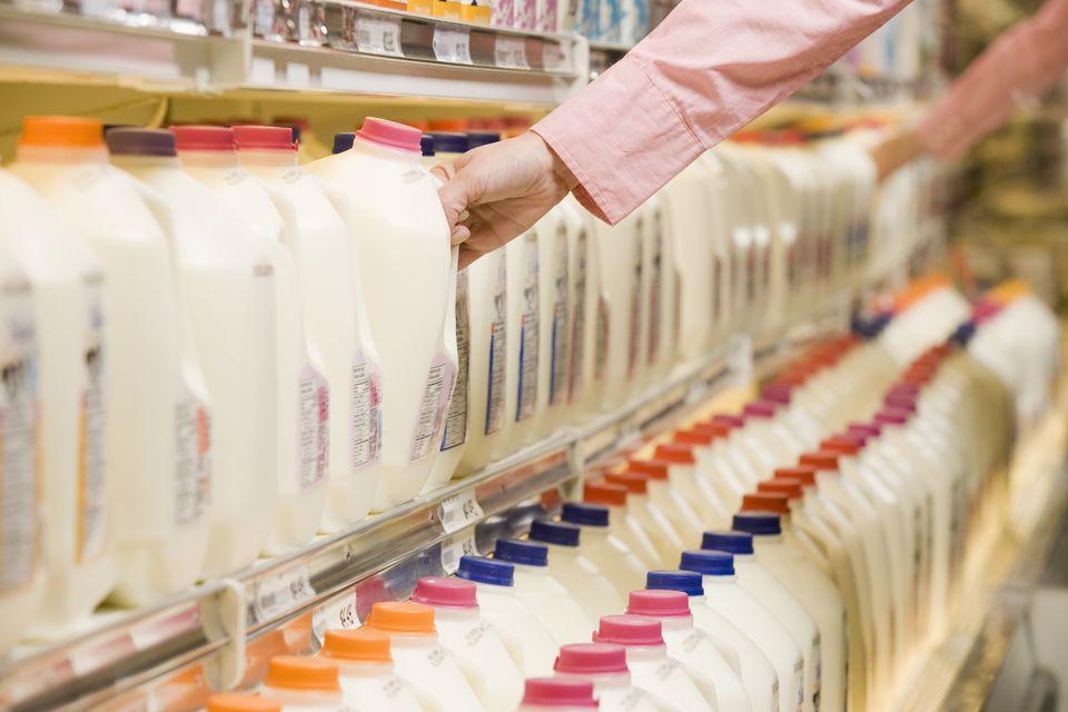 Person lifting milk jug from dairy aisle shelf