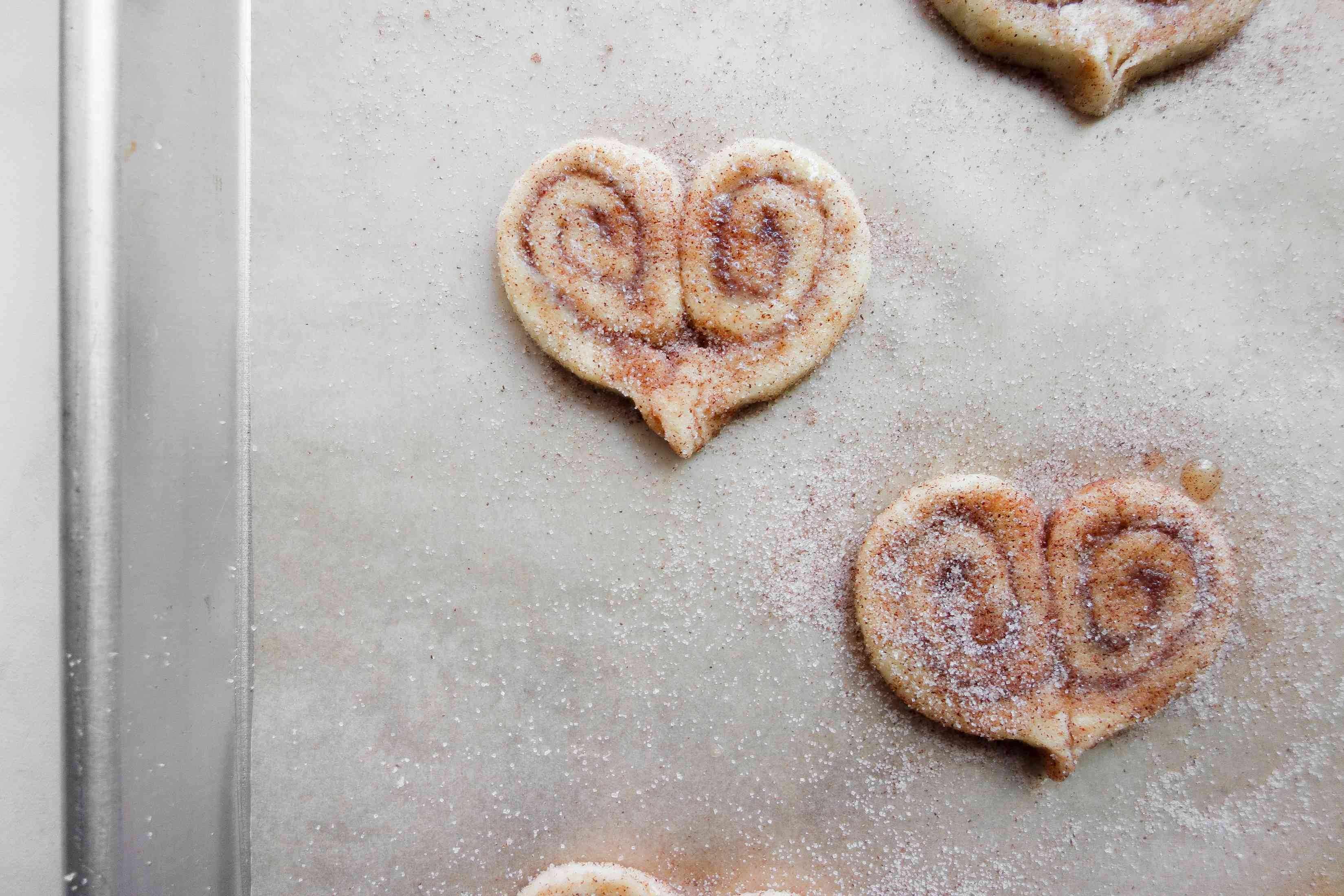 puff pastry hears on a baking sheet, covered with cinnamon sugar