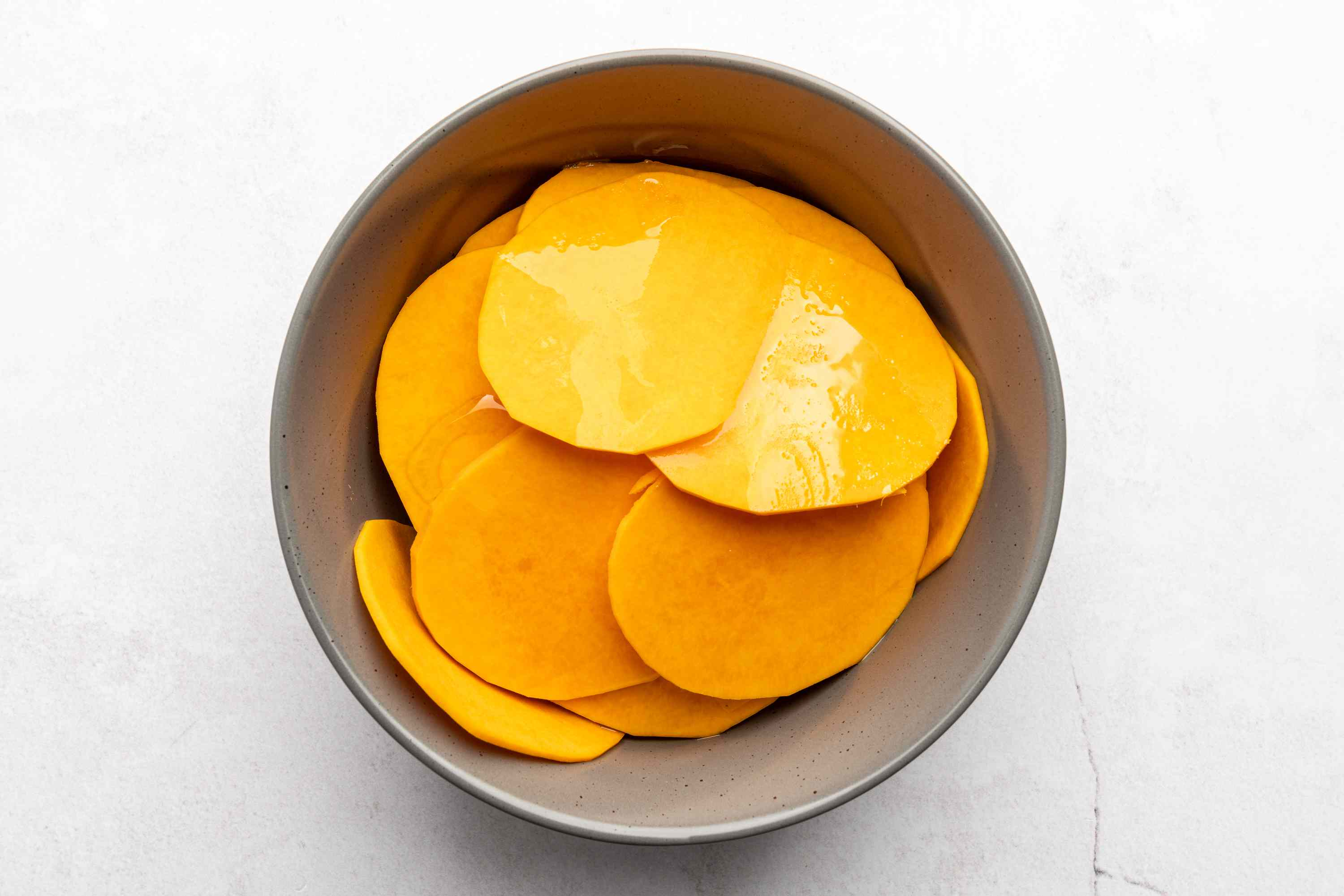 squash slices and oil in a bowl