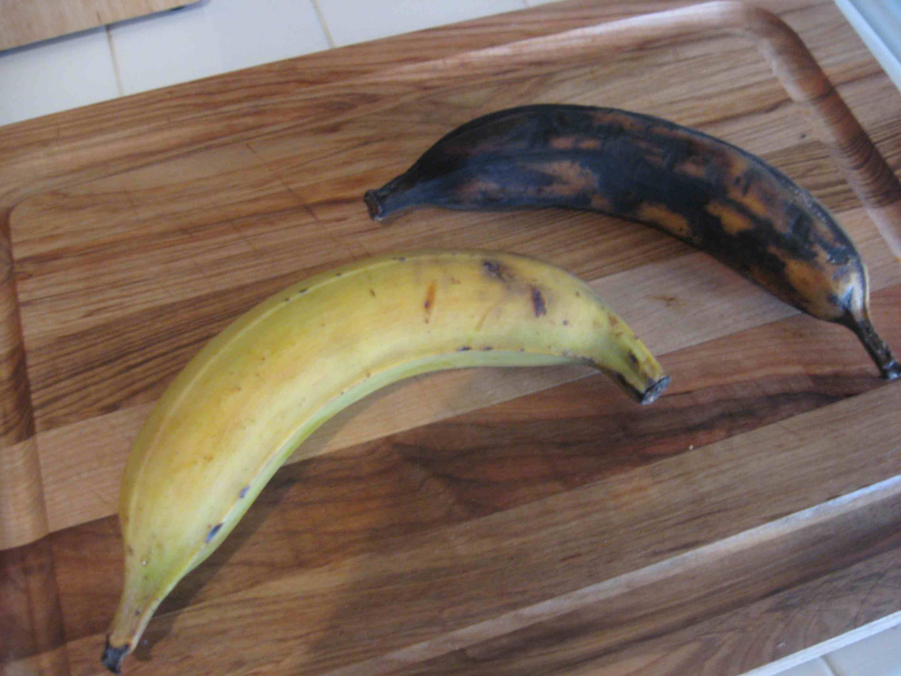 Ripe and over ripe plantains on a cutting board.