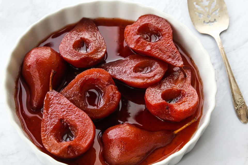 Poached pears in red wine in a white bowl