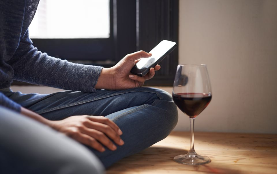 using phone with glass of wine
