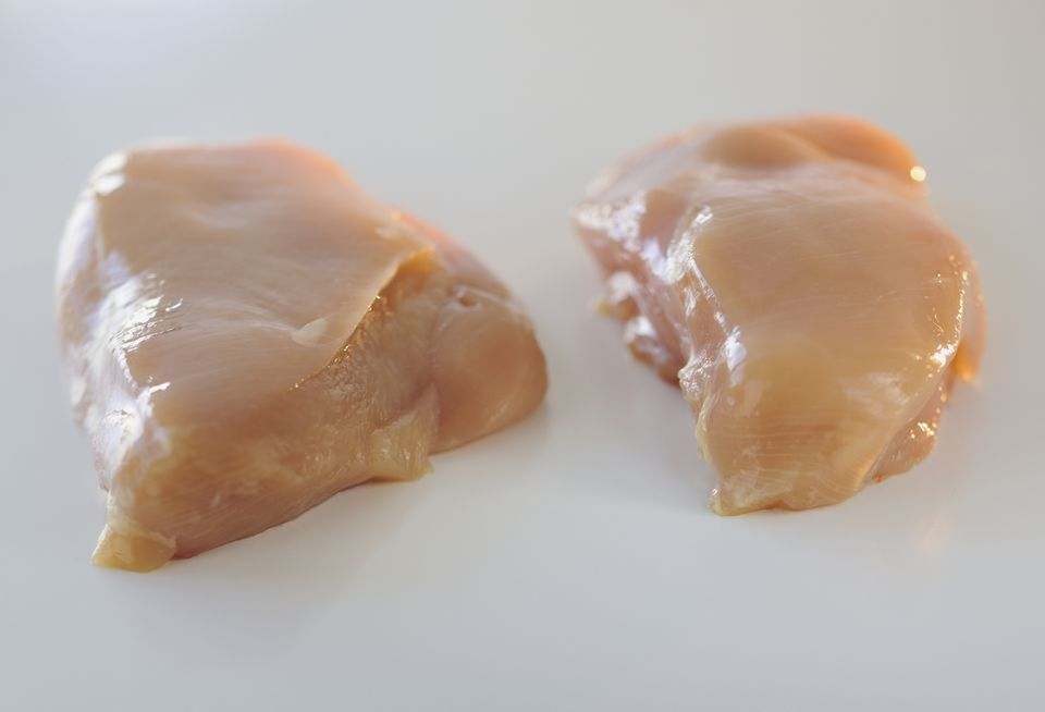 Raw chicken breasts on counter