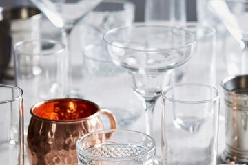 Collection of different types of bar glasses including rocks, mule, and margarita glasses.