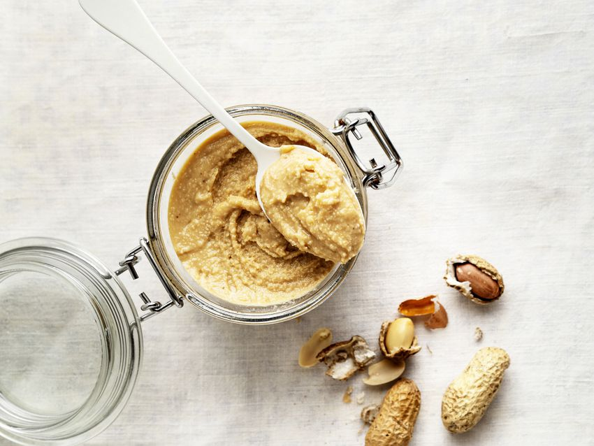 a spoonful of peanut butter over a jar next to peanuts