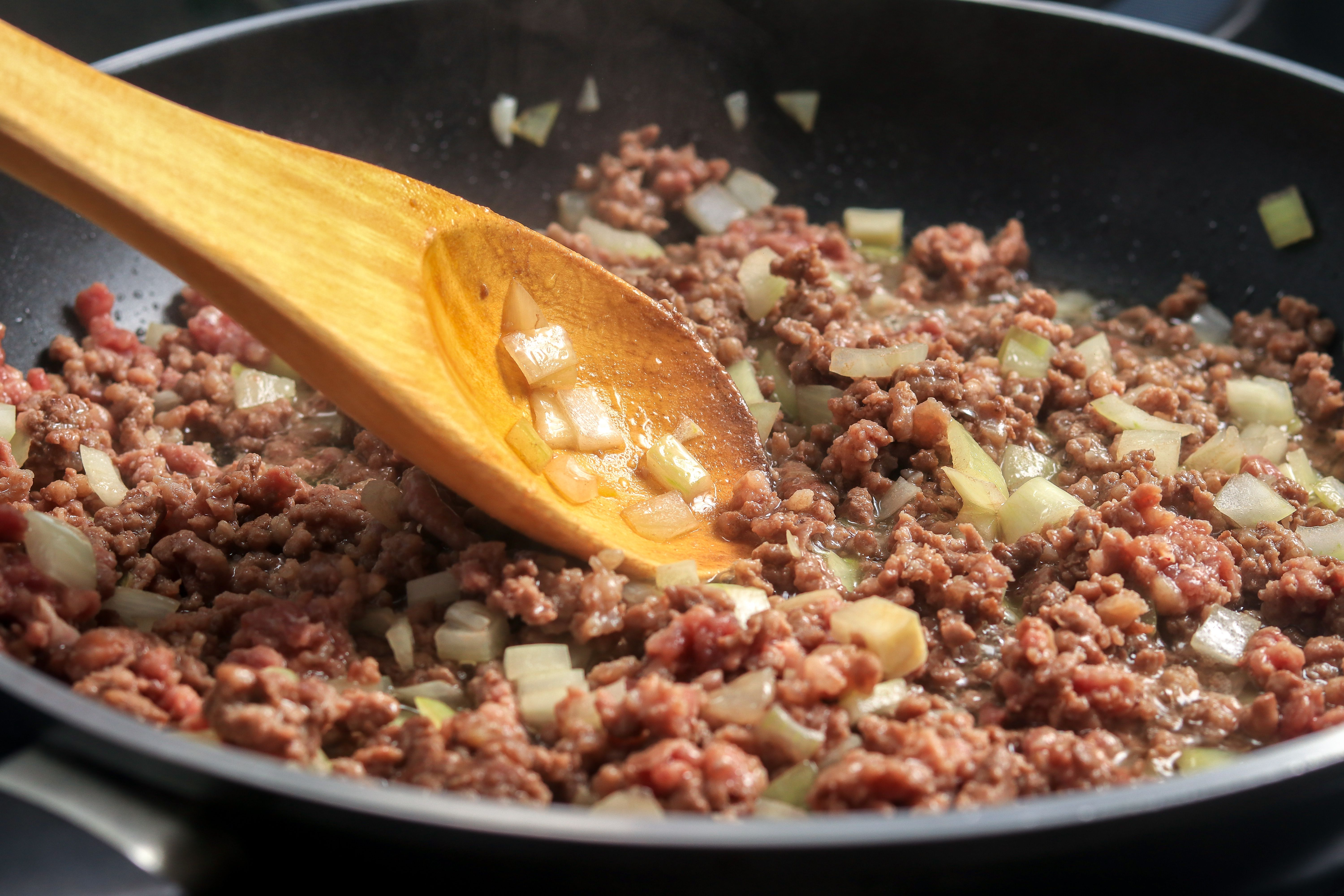 Ground beef and onions in frying pan