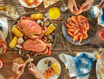 overhead of hands peeling seafood at seafood boil