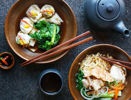 Asian noodles and dumplings in bowls with chopsticks along with tea and teapot