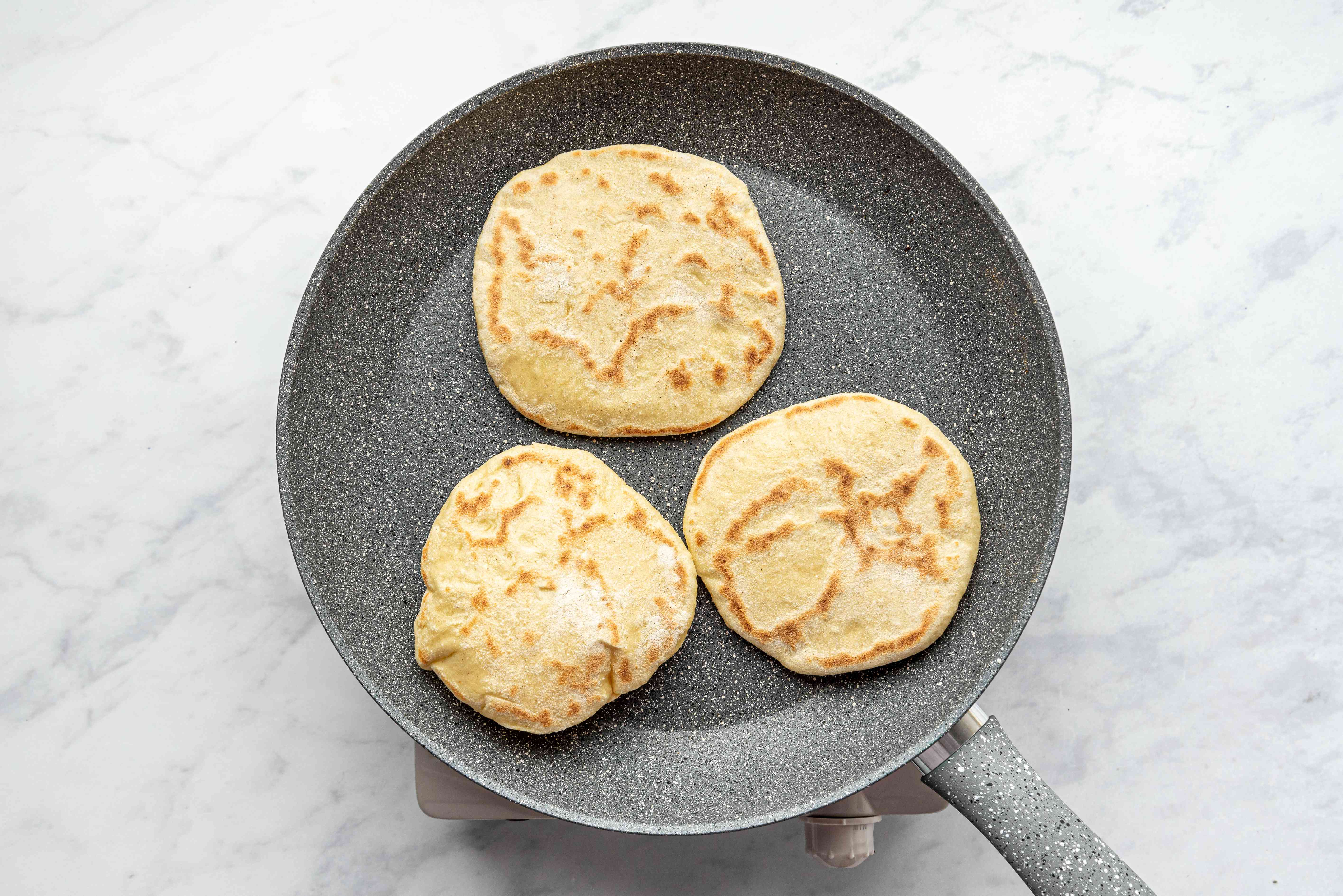 pita bread cooking in a skillet