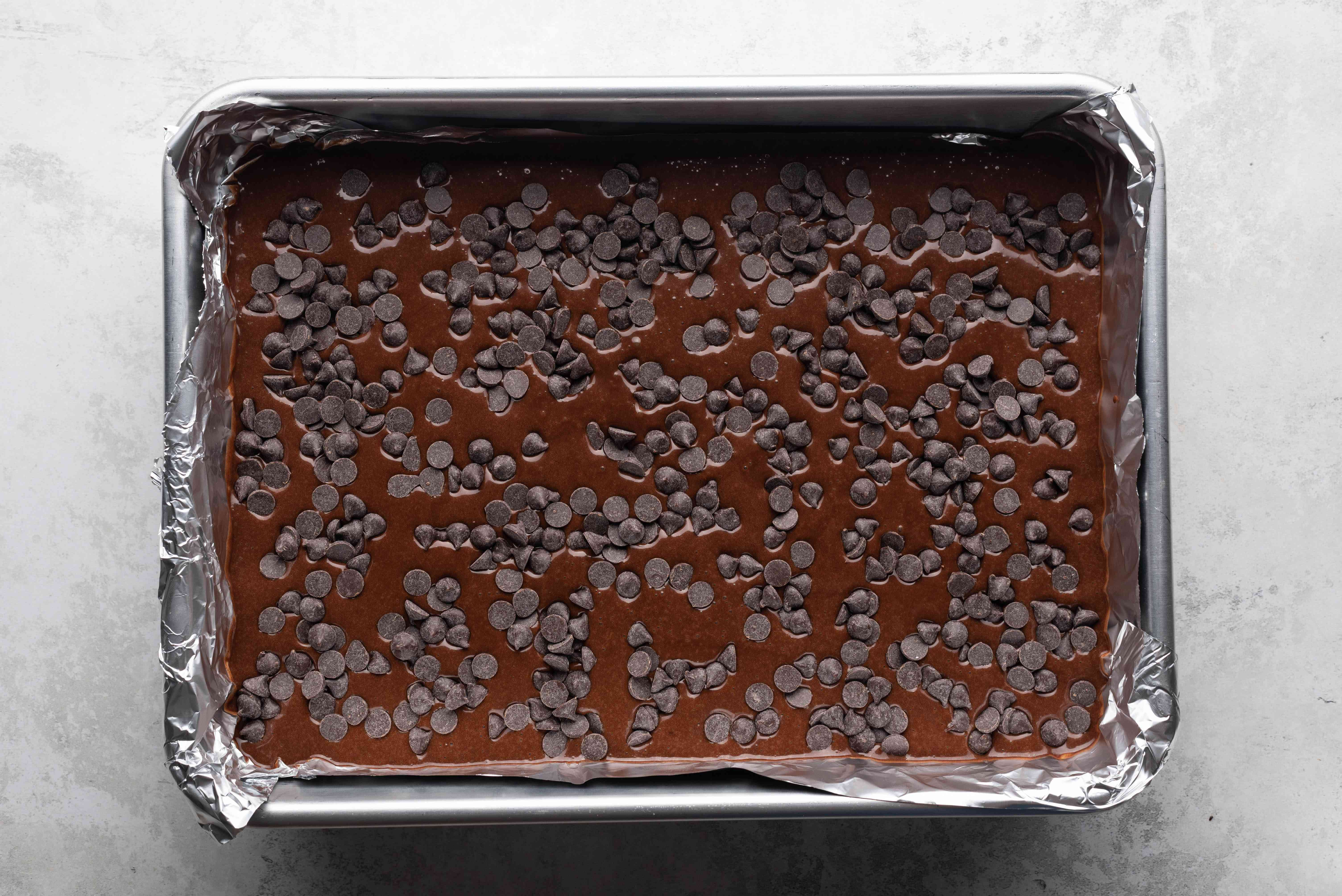 brownie batter in a baking pan, chocolate chips on top