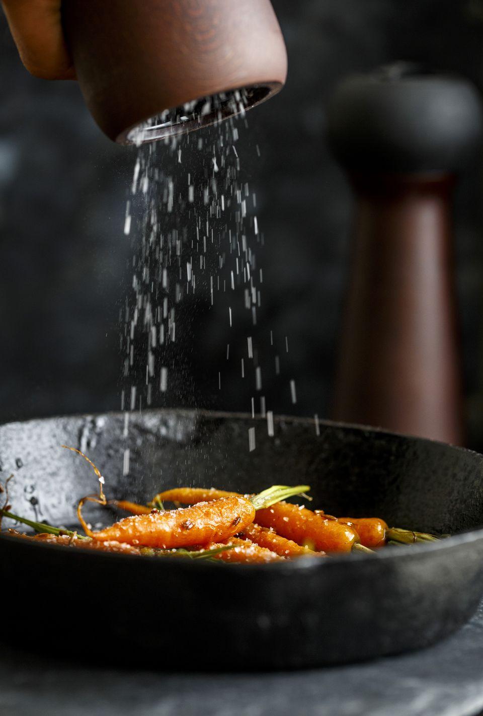 Glazed Carrots on a cast iron pan, salt sprinkled