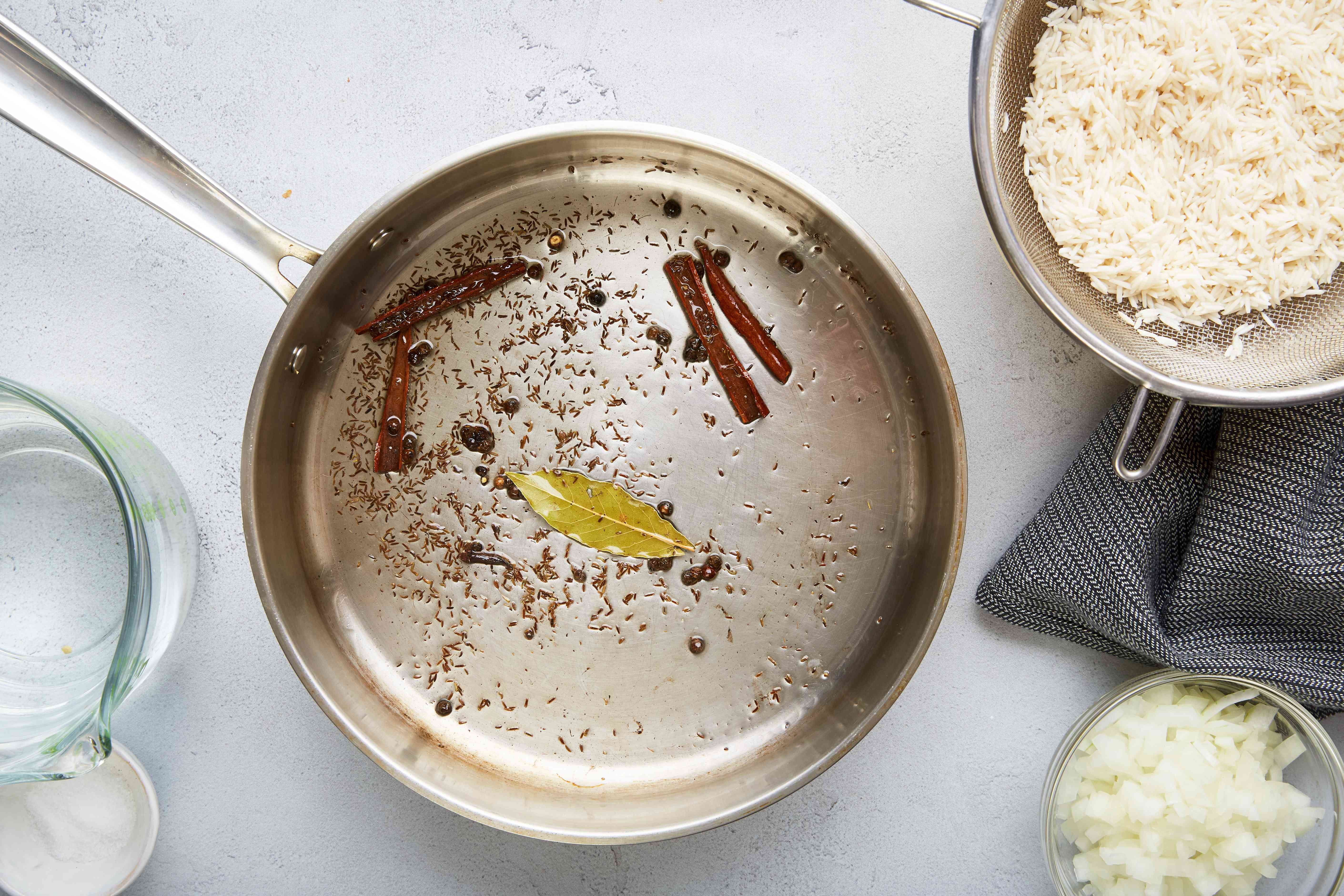 Olive oil in pan with cinnamon, bay leaf, cumin, and cloves