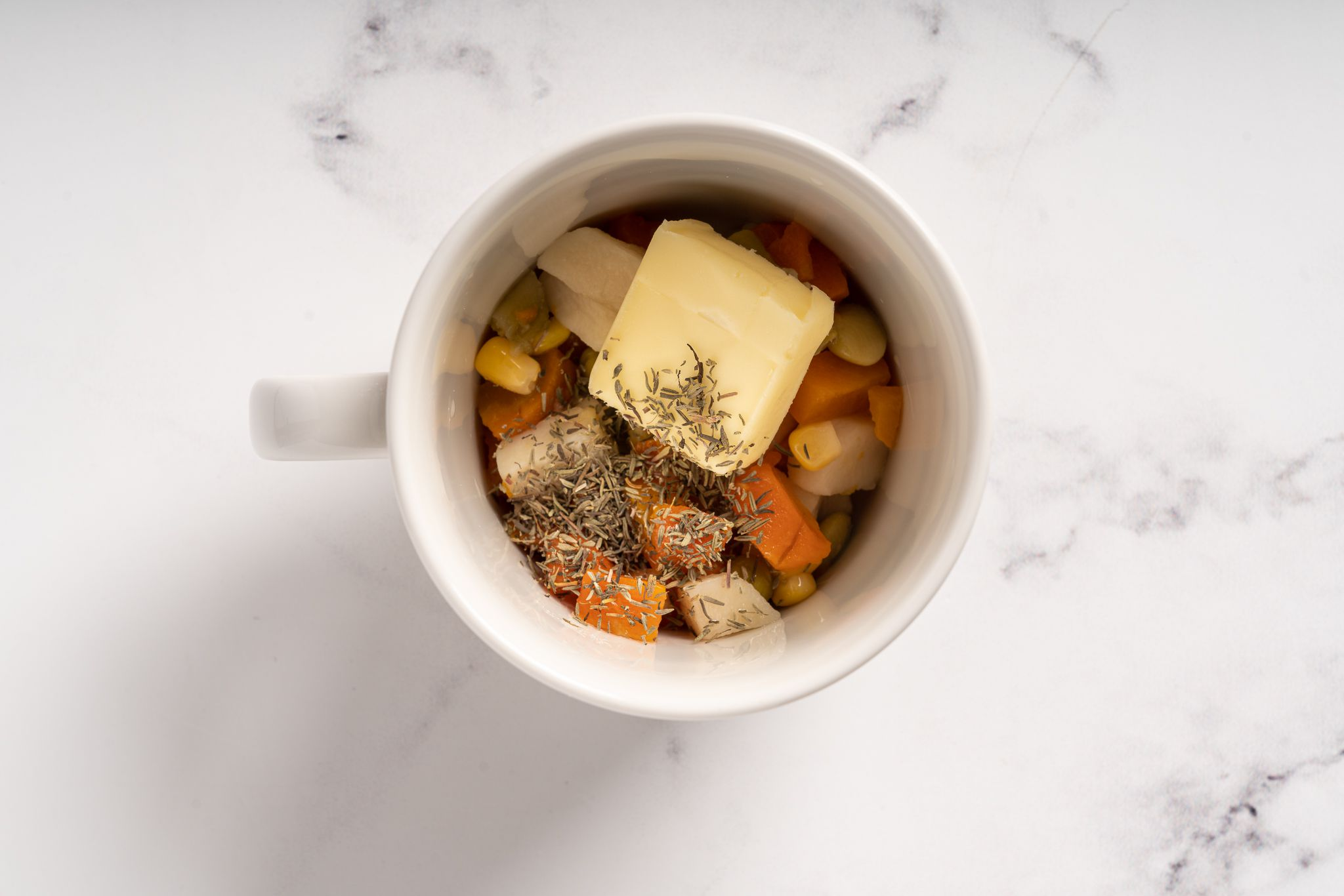 Vegetables, butter, and thyme in a mug