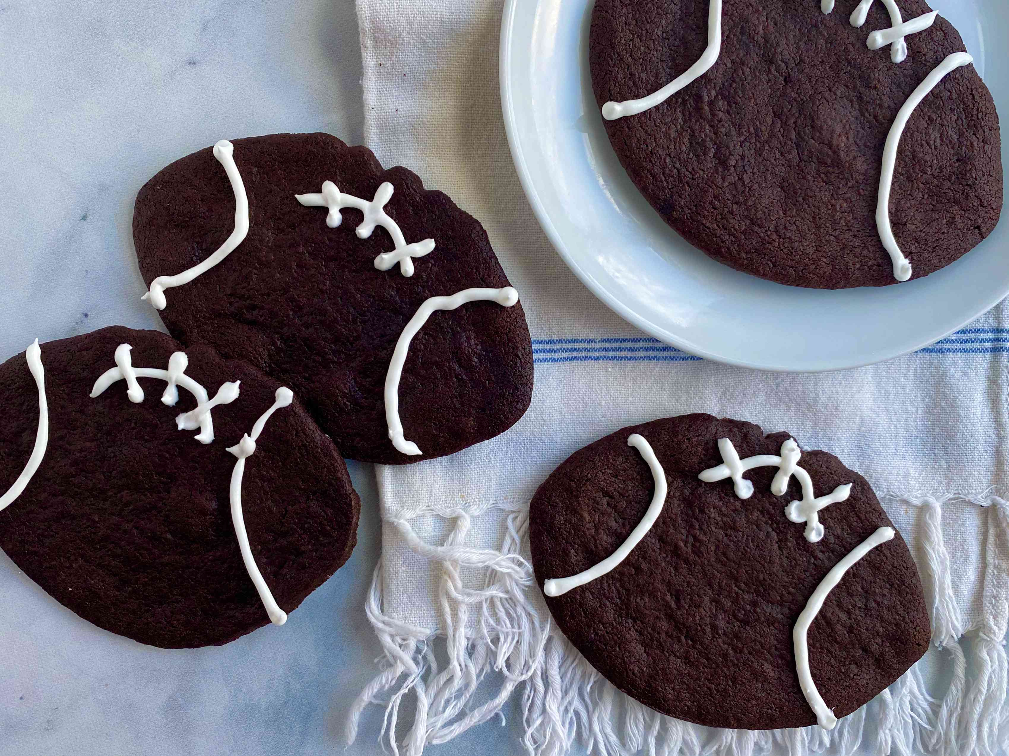 Chocolate football-shaped cookies with icing laces