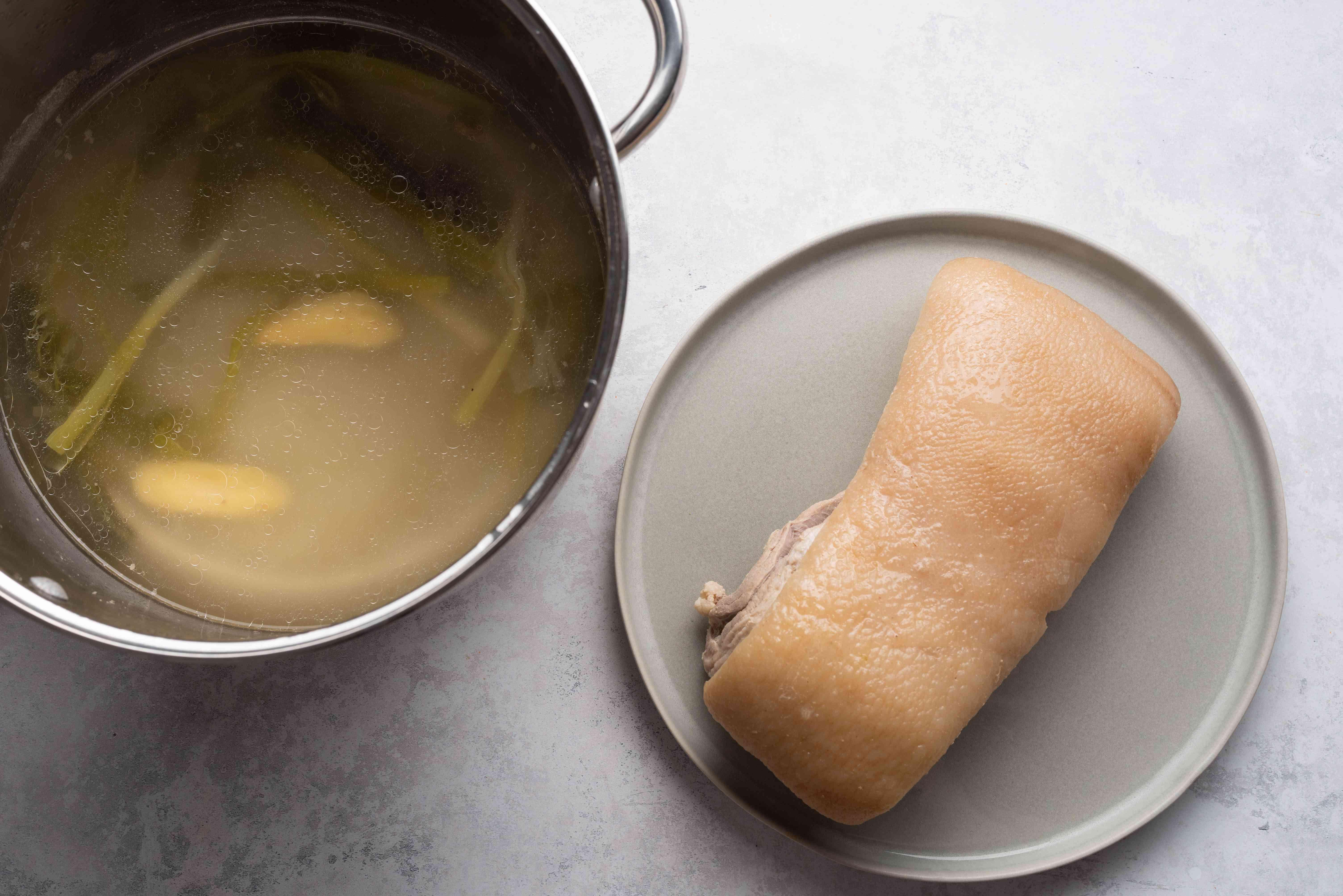pork belly boiled, resting on plate, stock in pot