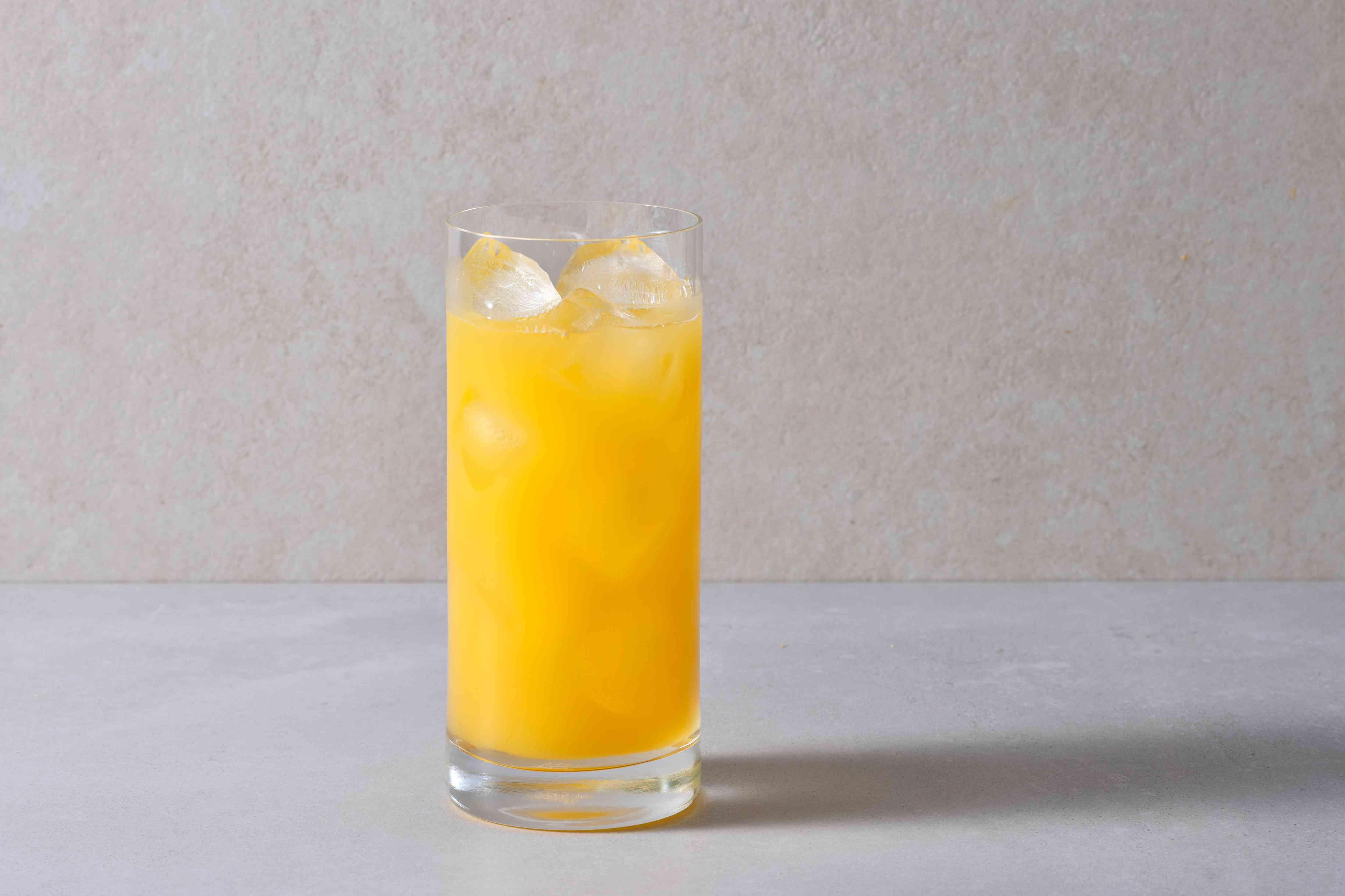 Pour the vodka, amaretto, and orange juice into a tall Collins glass filled with ice