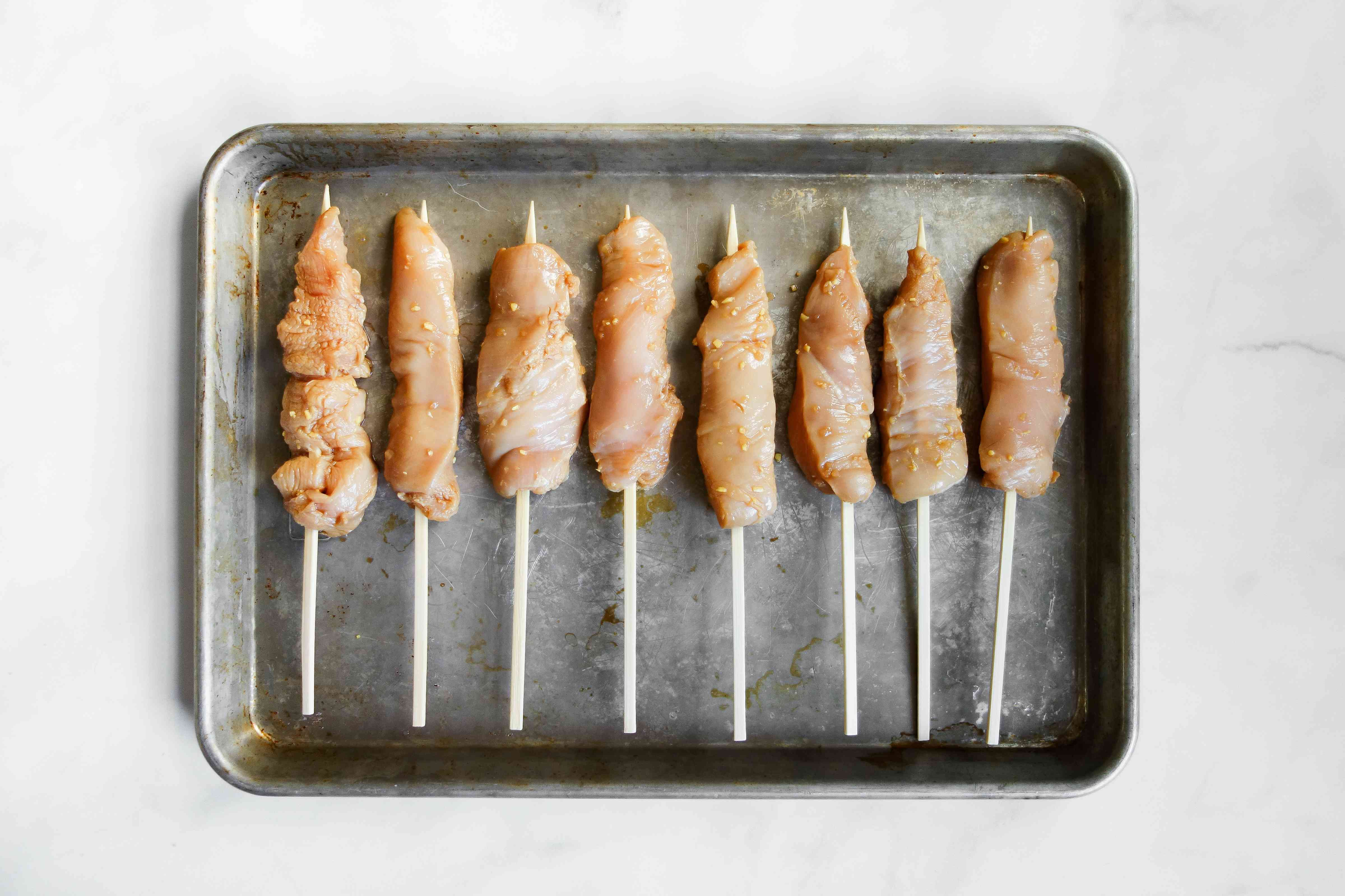 Thread chicken strips onto the pre-soaked skewers on a baking sheet