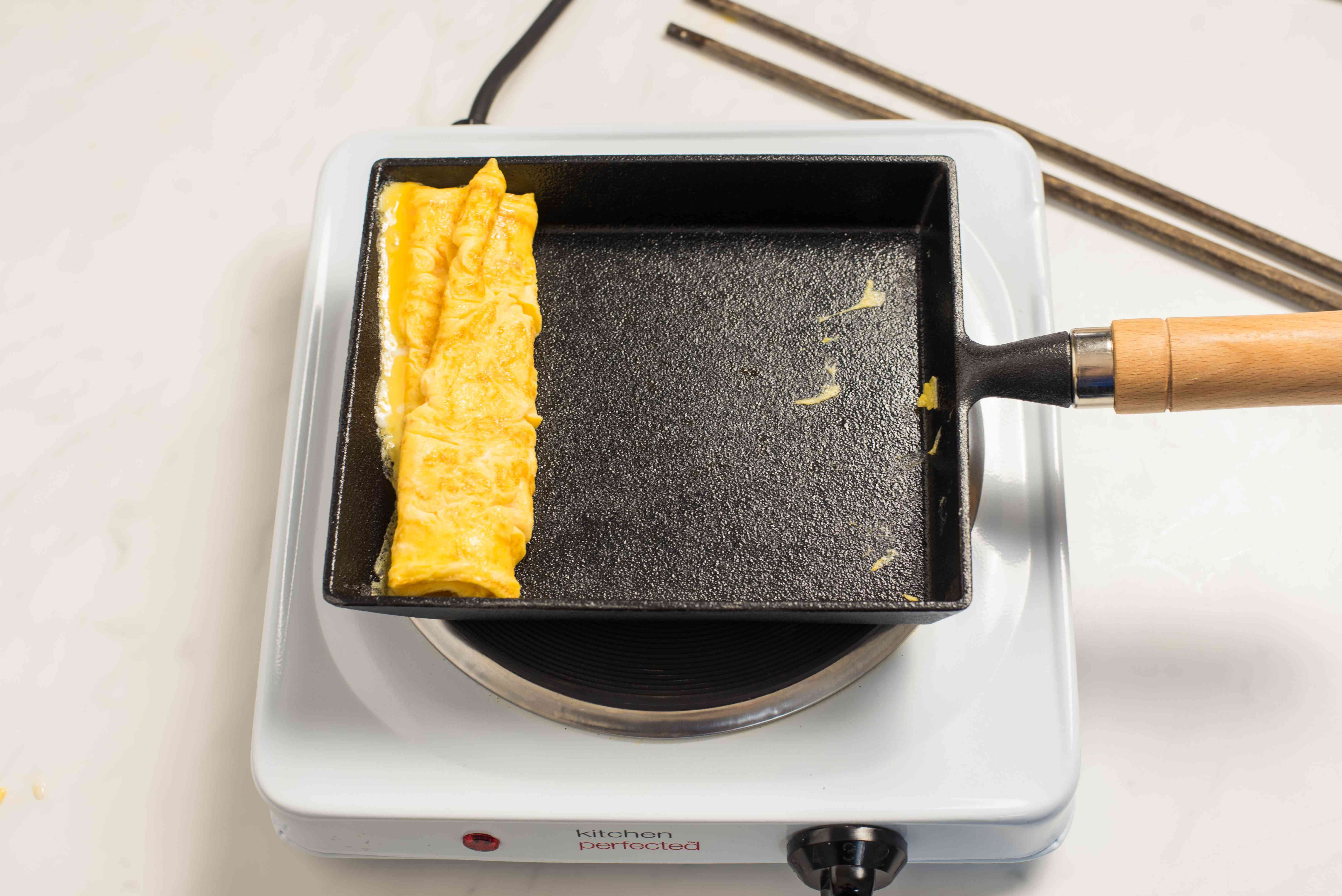 Cook until halfway done, then roll toward bottom of pan