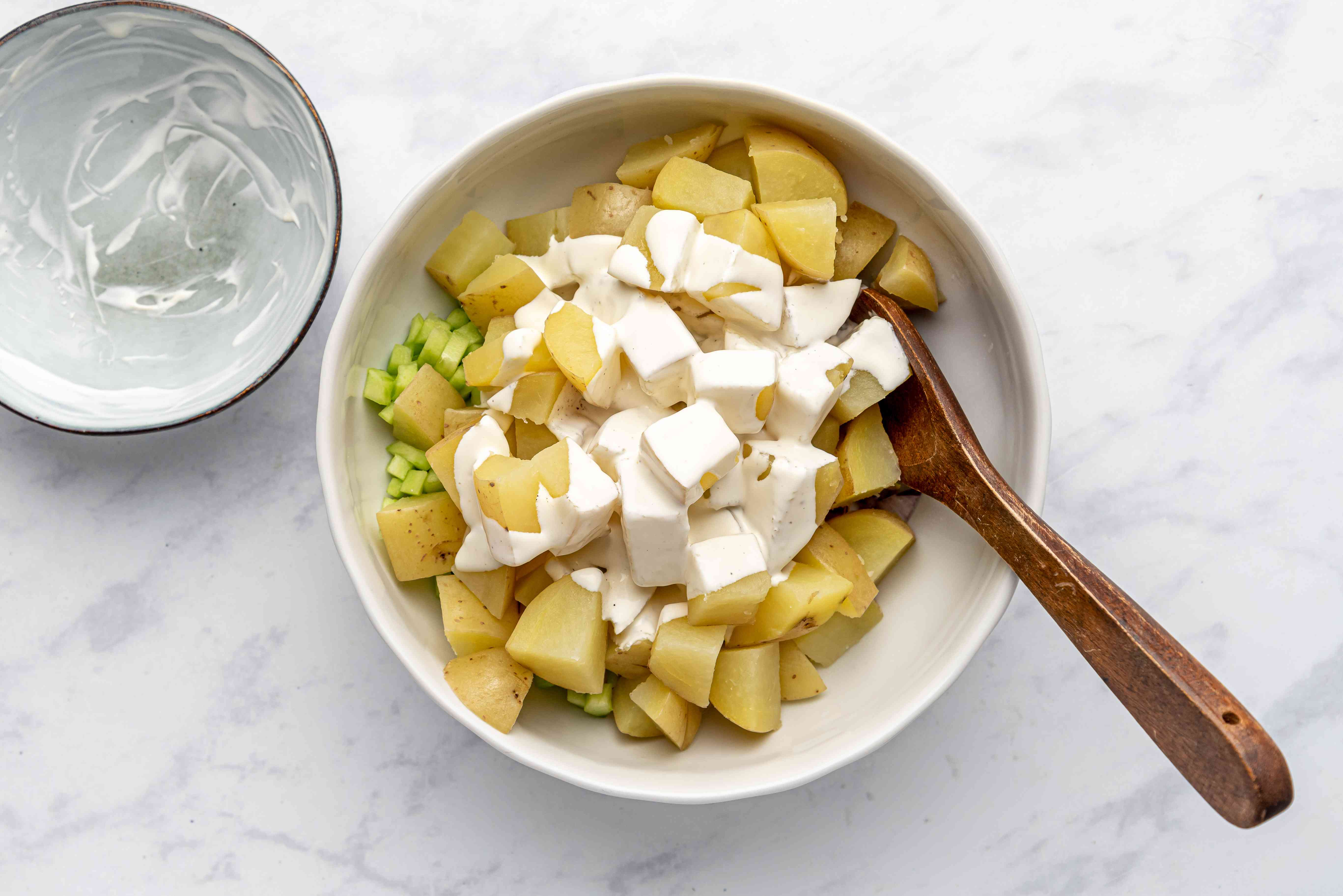 Fingerling Potato Salad, mixing dressing with the vegetable mixture in the bowl