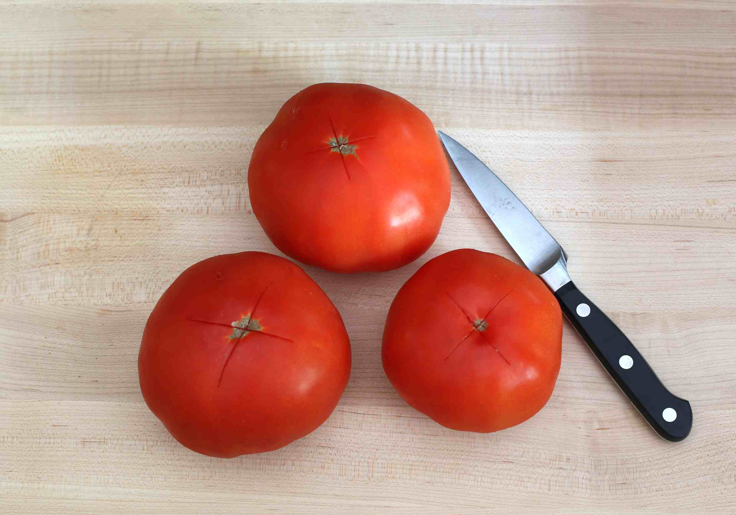Tomatoes and knife on wood table