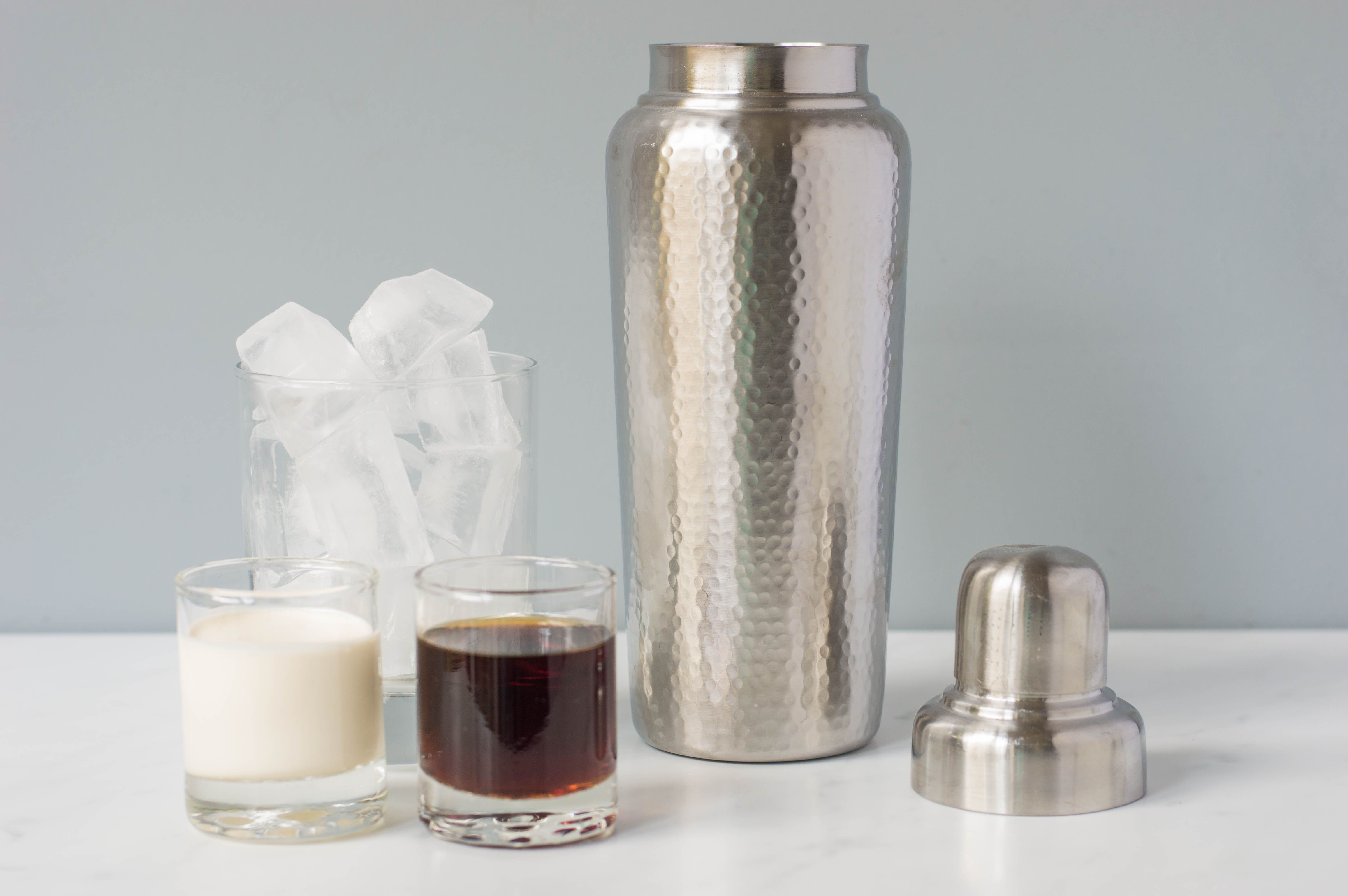 Cream and coffee liqueur in separate glasses next to a cocktail shaker