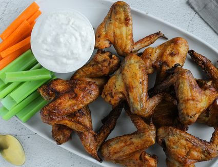 Salt and vinegar wings on a plate with carrot and celery sticks with dip