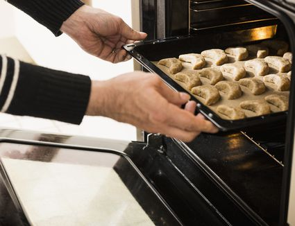 Close-up of a man putting baking tray of vanilla crescents in oven for baking, Munich, Bavaria, Germany