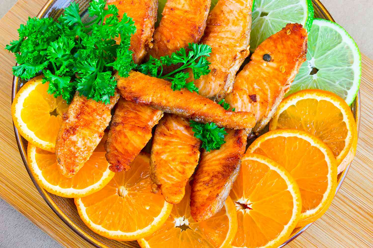 Fried salmon fillet with lime, mandarins and parsley.