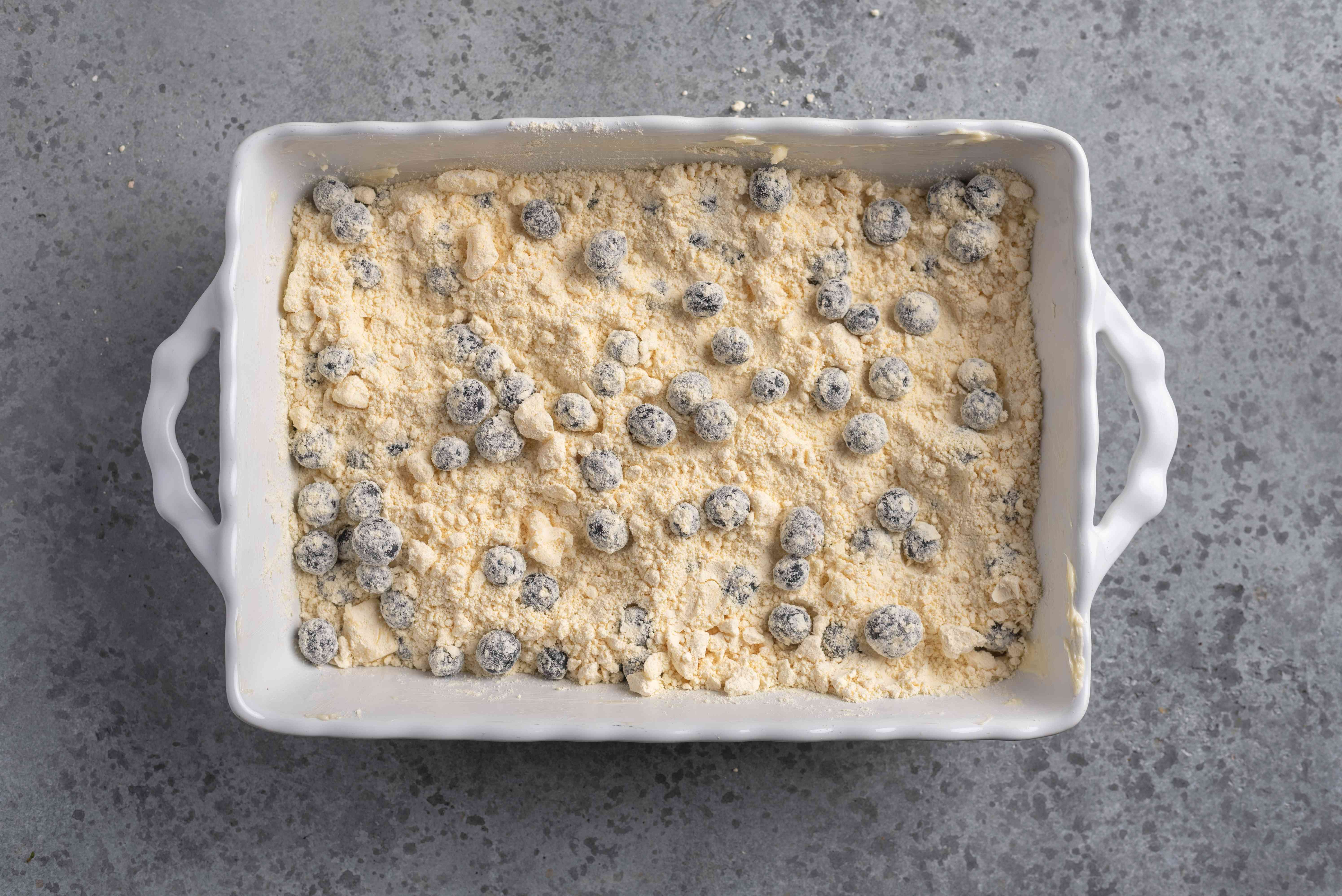 Blueberries with the butter and flour mixture in the baking dish