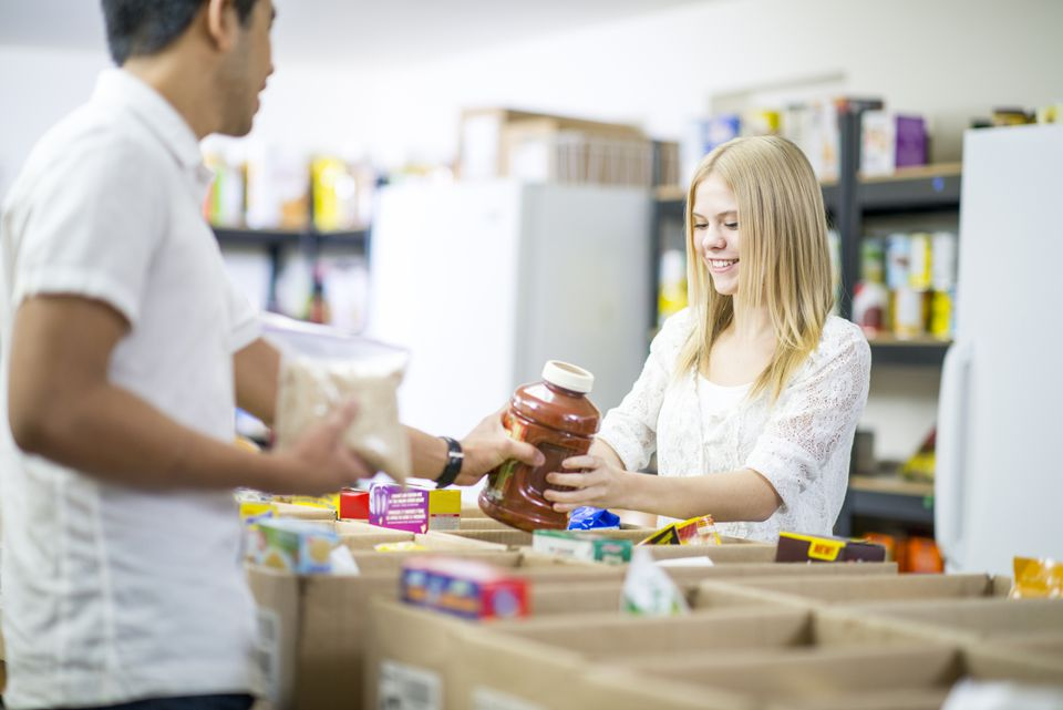 Man and teenage girl sorting food at foodbank