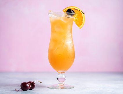 Classic hurricane cocktail with a cherry and orange slice garnish