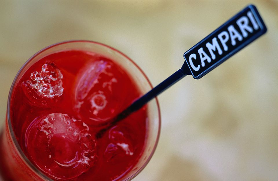 A Campari swizzle stick sticking out of a glass of Campari and soda in a bar - Noosa, Queensland