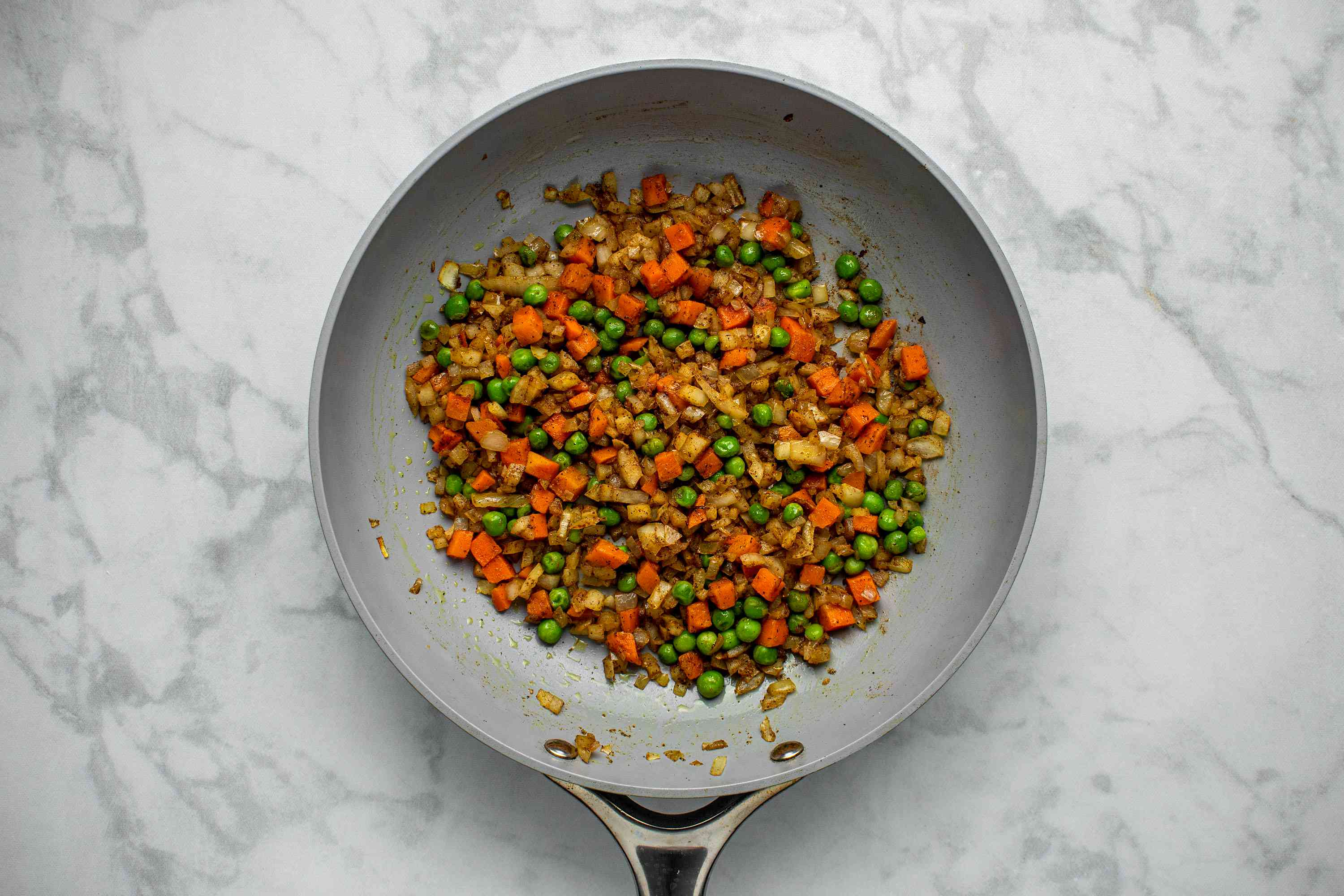 Add the peas and carrots, garam masala, and curry powder to the onions in the skillet