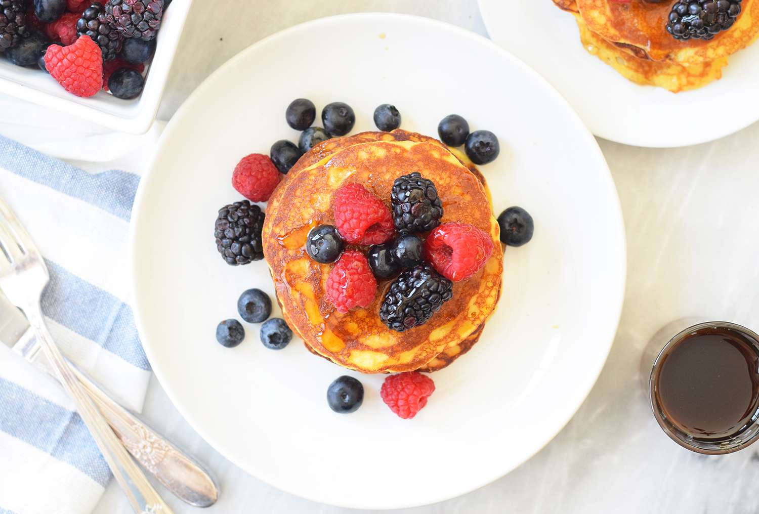 Coconut flour pancakes on a serving plate with fresh berries