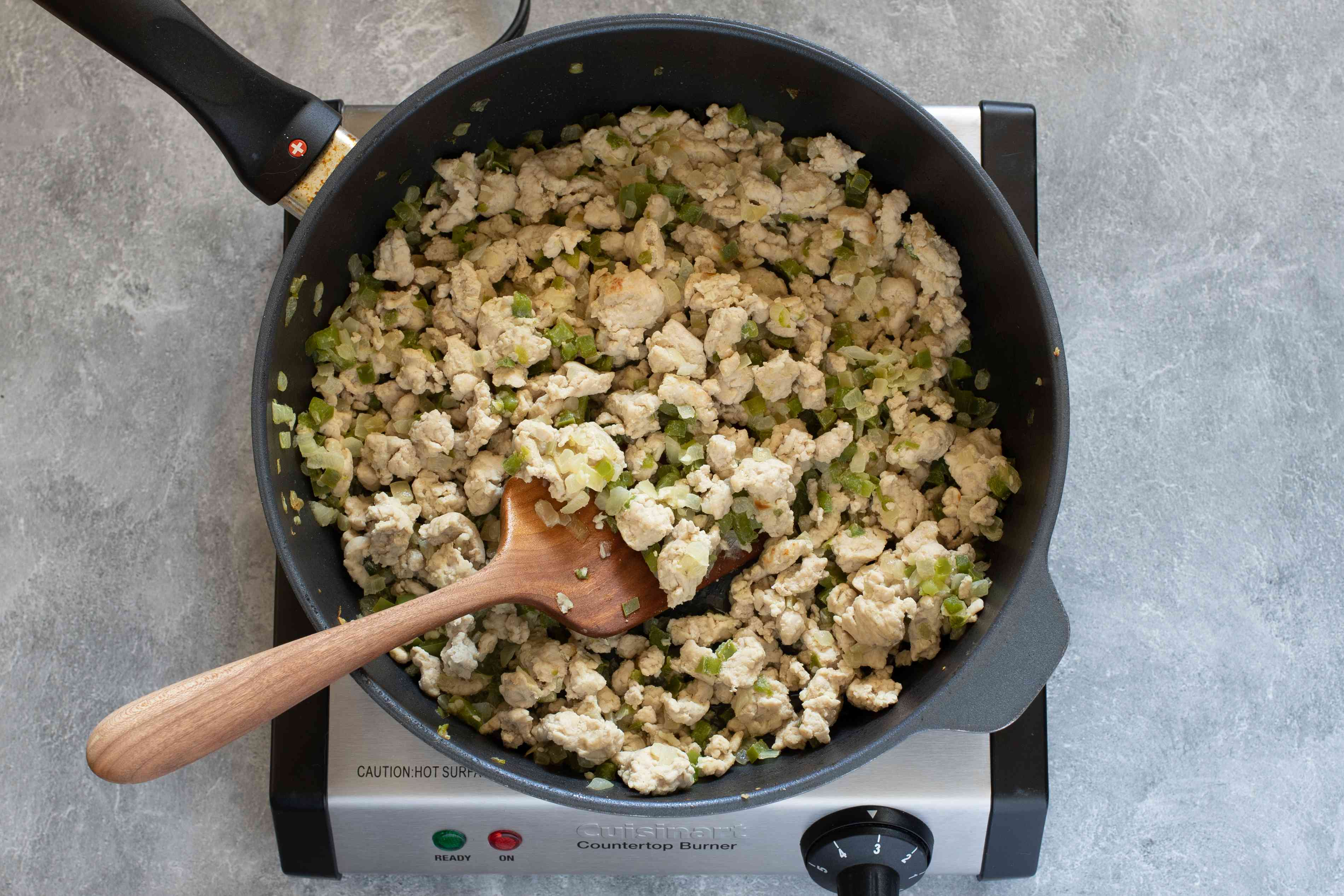 Saute pan with cooked ground turkey