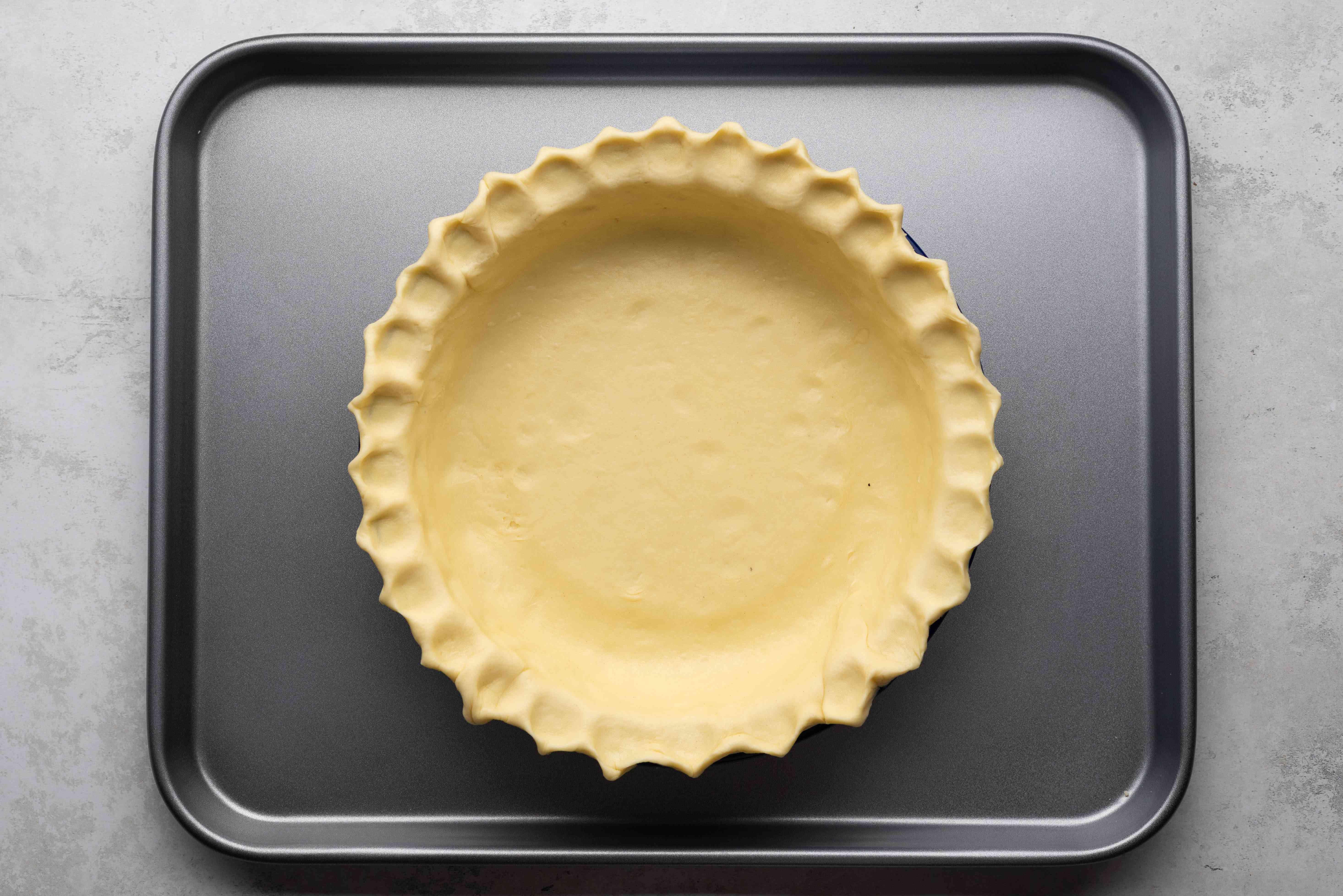 pie crust on in a pie pan on a baking sheet