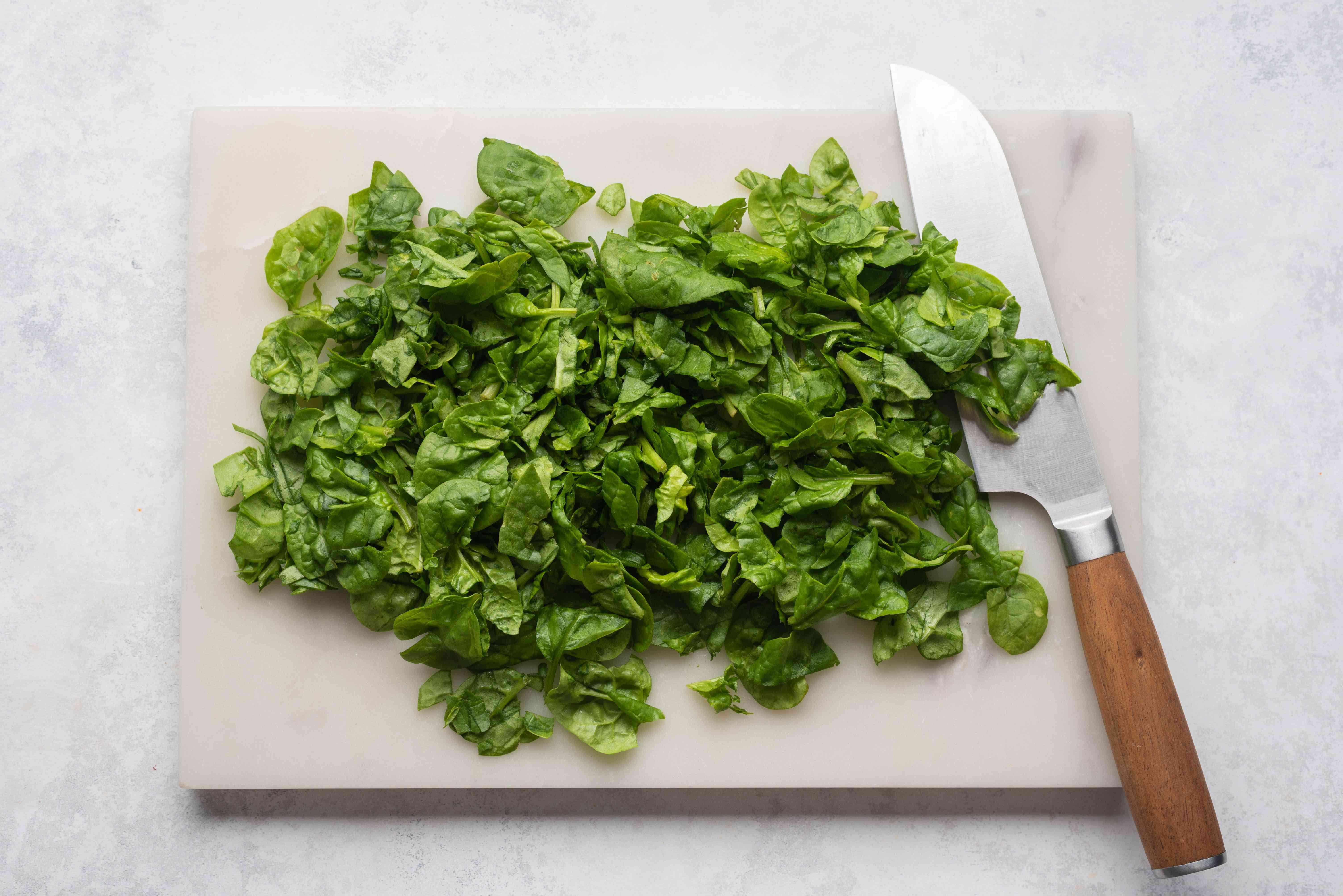 chop spinach on a cutting board