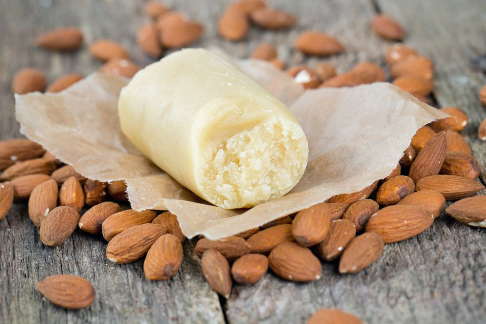 A roll of marzipan on a bed of almonds