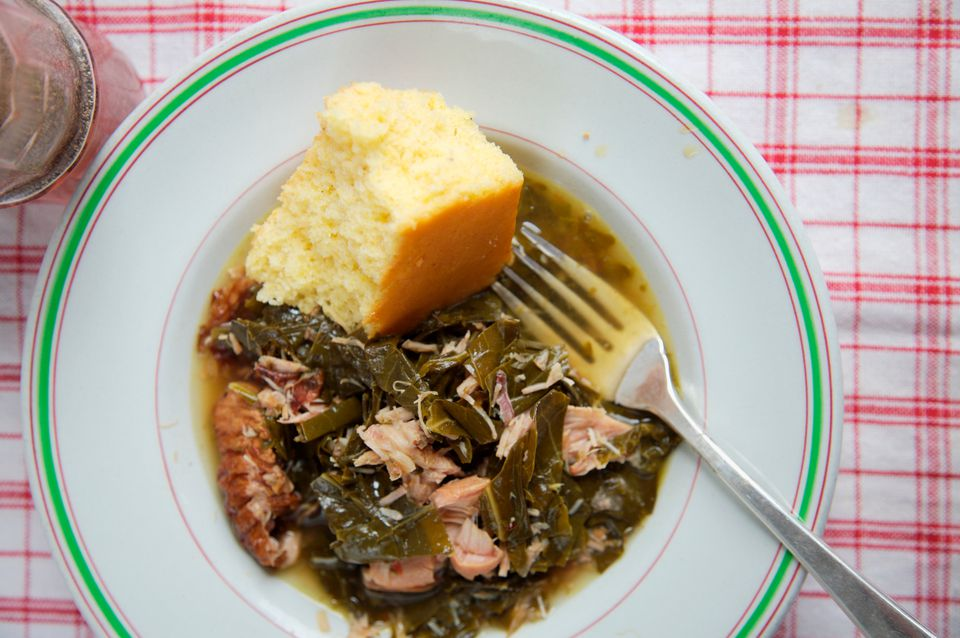 Plate of collard greens with smoked turkey wings and corn bread.