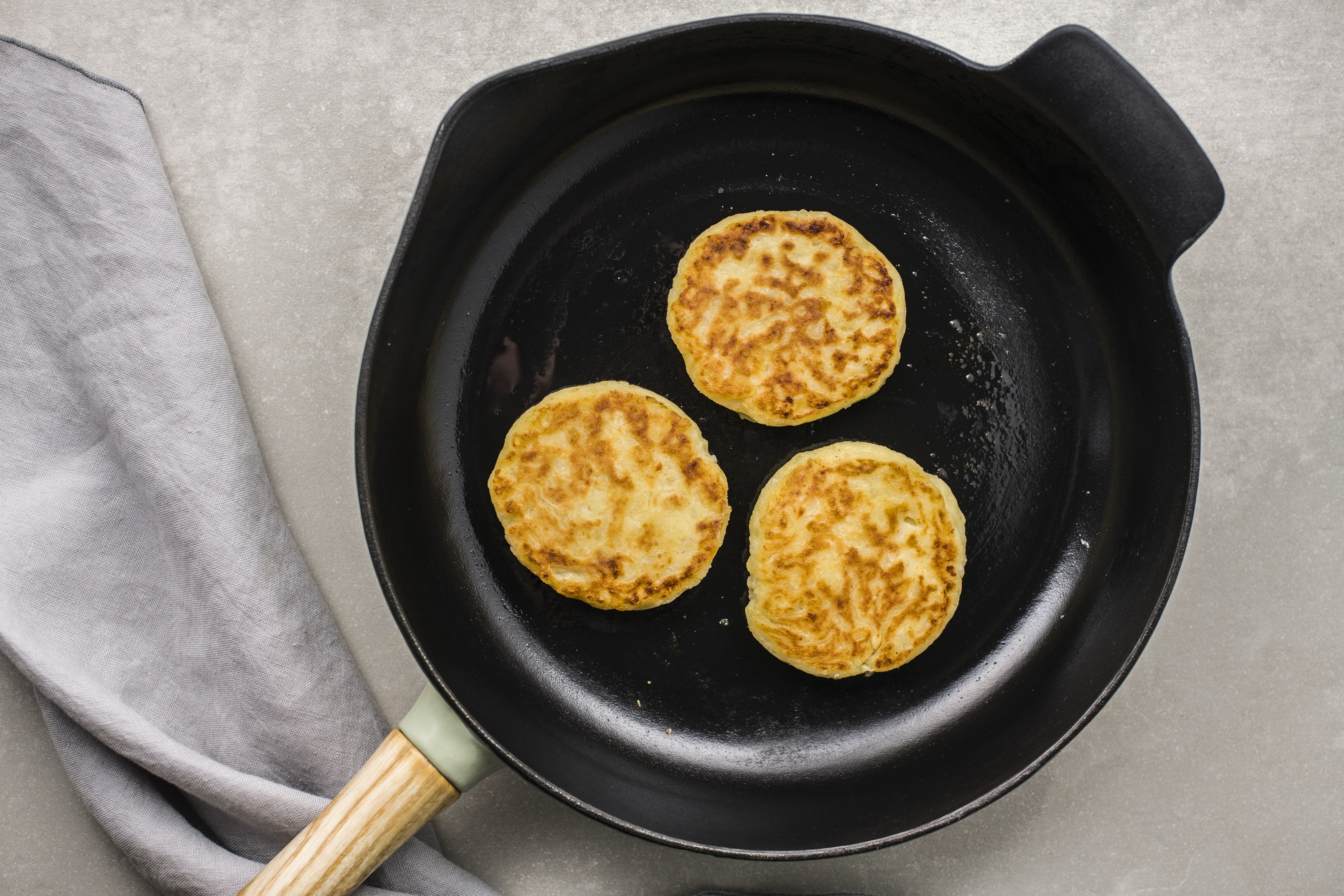 Potato patties cooked on one side in a skillet