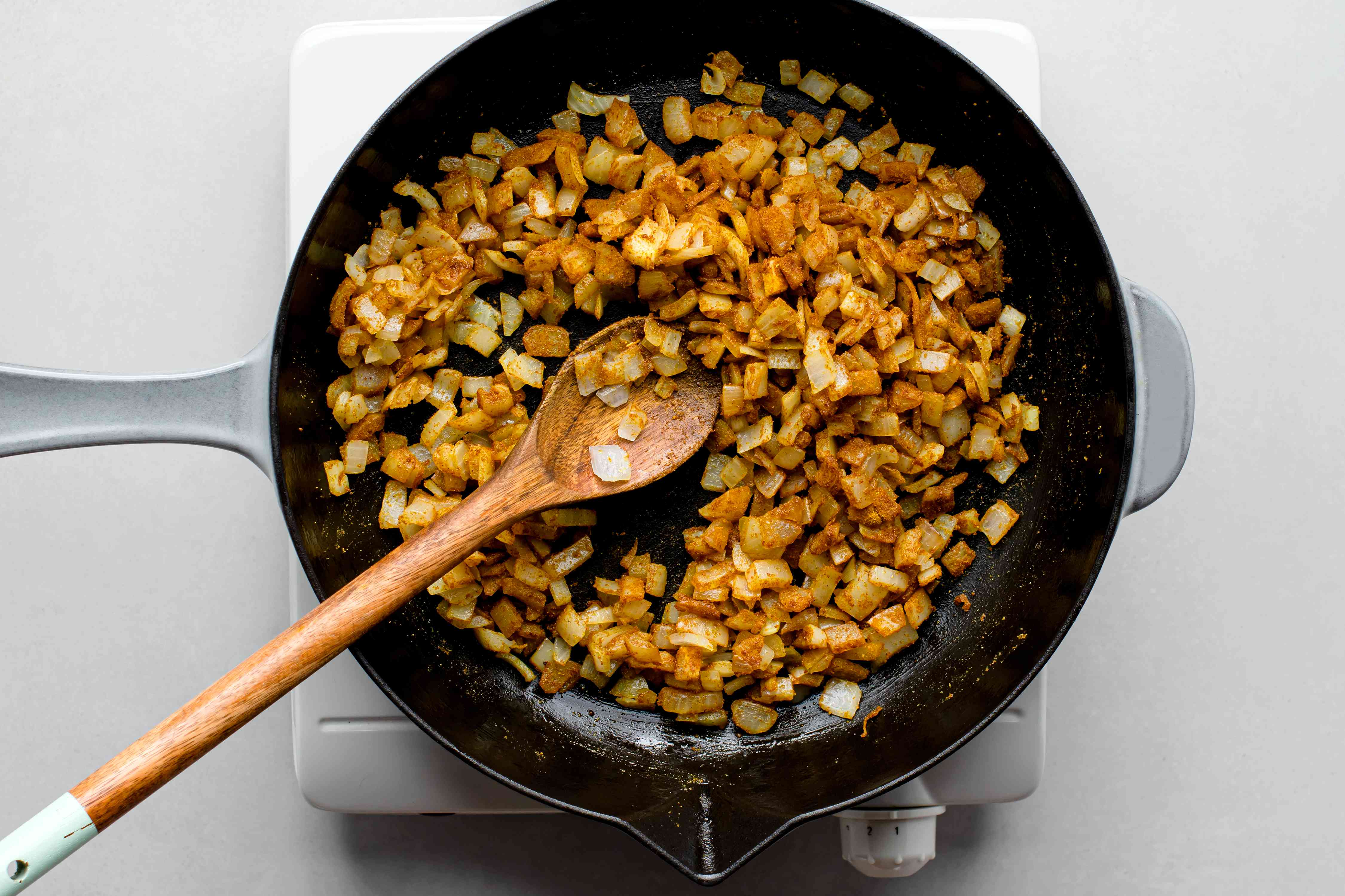 onions cooking with curry powder in a skillet