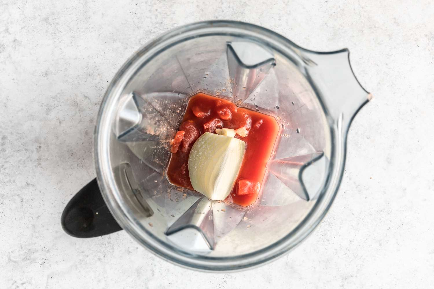 Place the tomatoes, onion, garlic, and salt into a blender