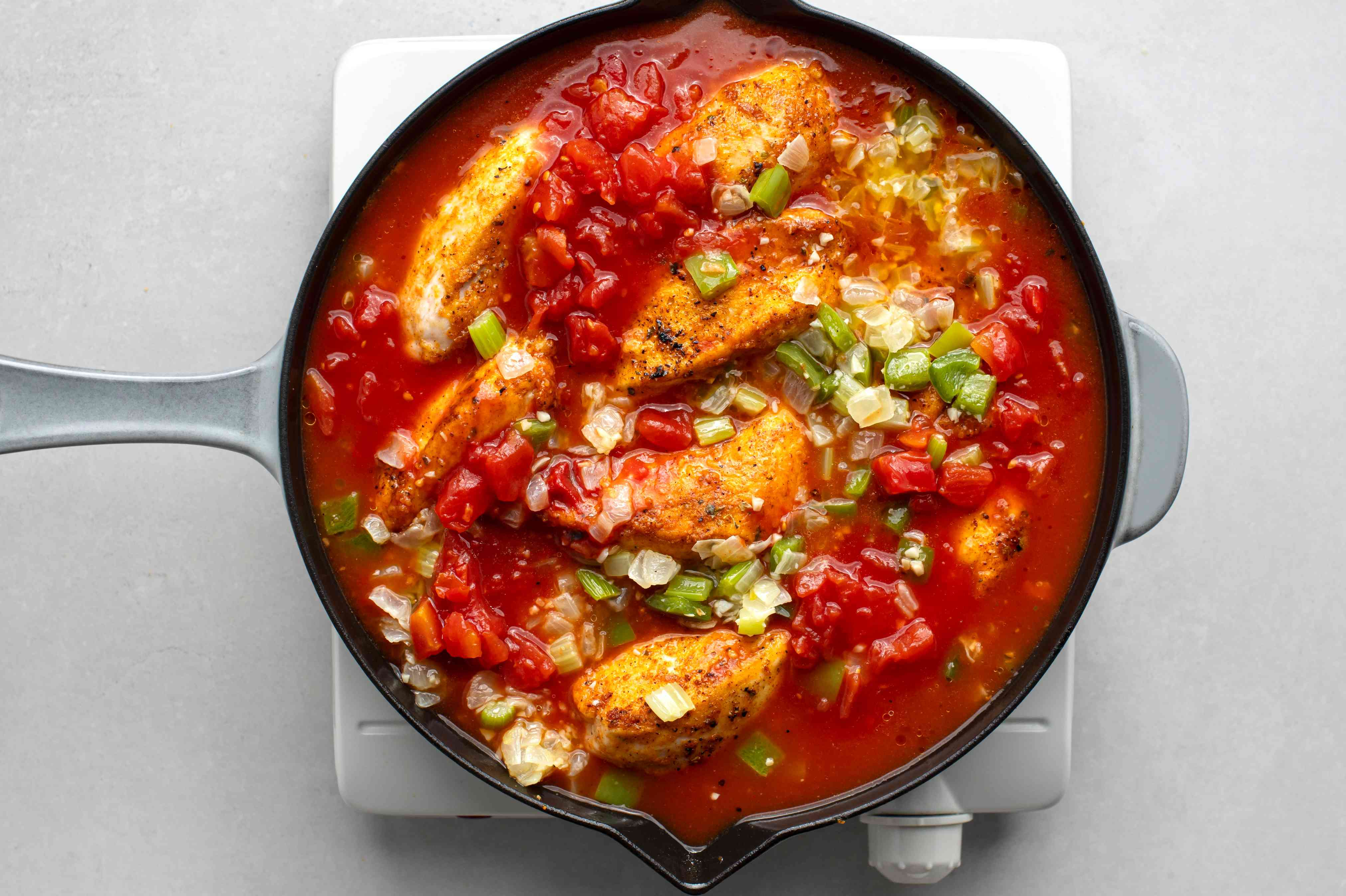 add chicken broth, tomatoes, and tomato paste to the chicken and vegetables in the skillet