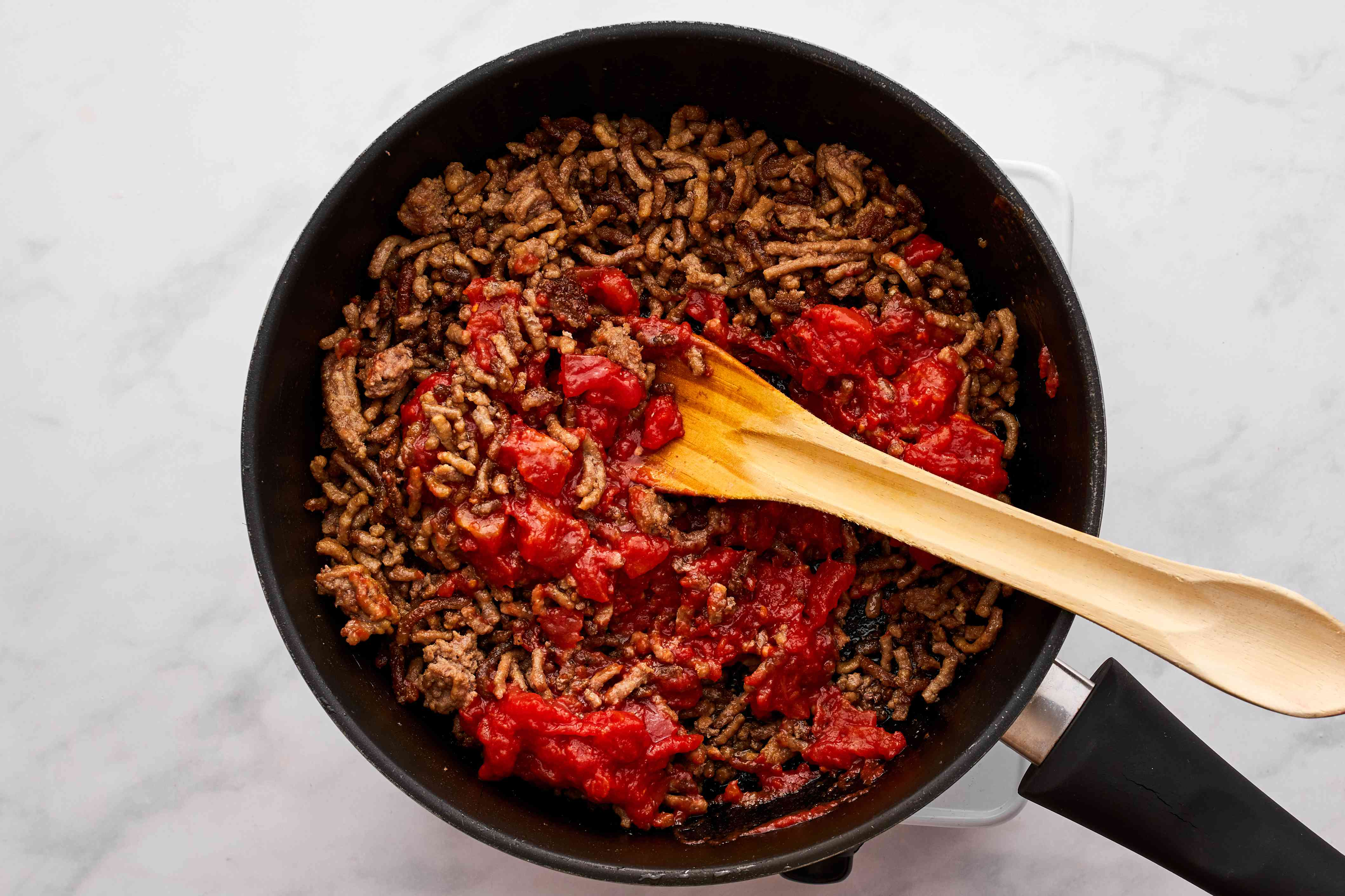 add tomatoes to the ground beef in the pan