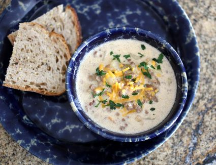 A bowl of cheeseburger chowder with bread