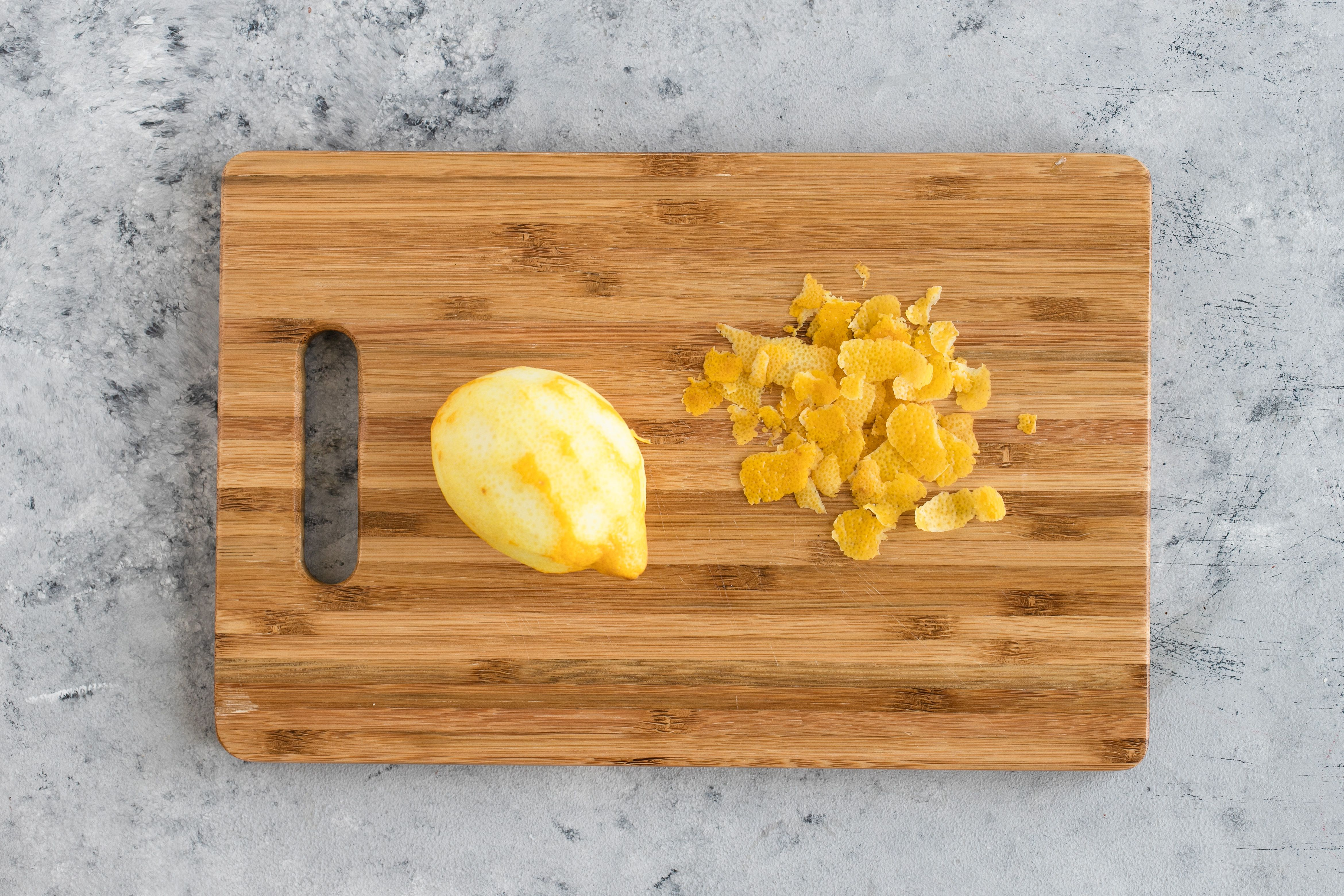 A zested lemon on a wooden cutting board