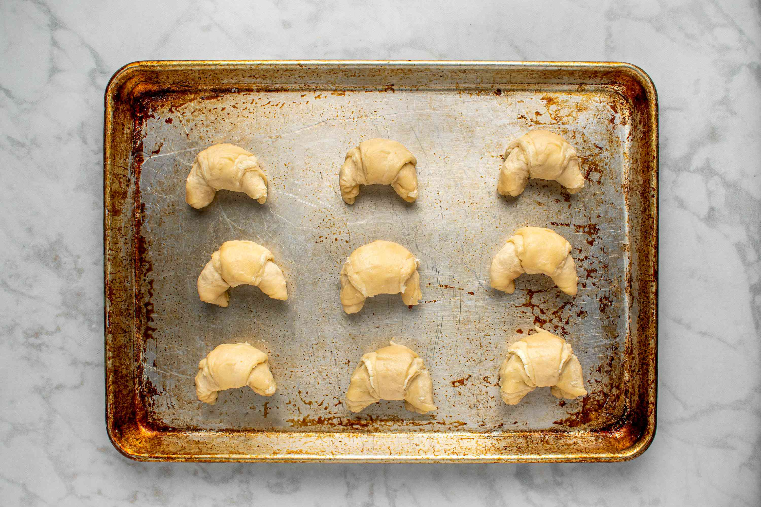unbaked croissants on a baking sheet
